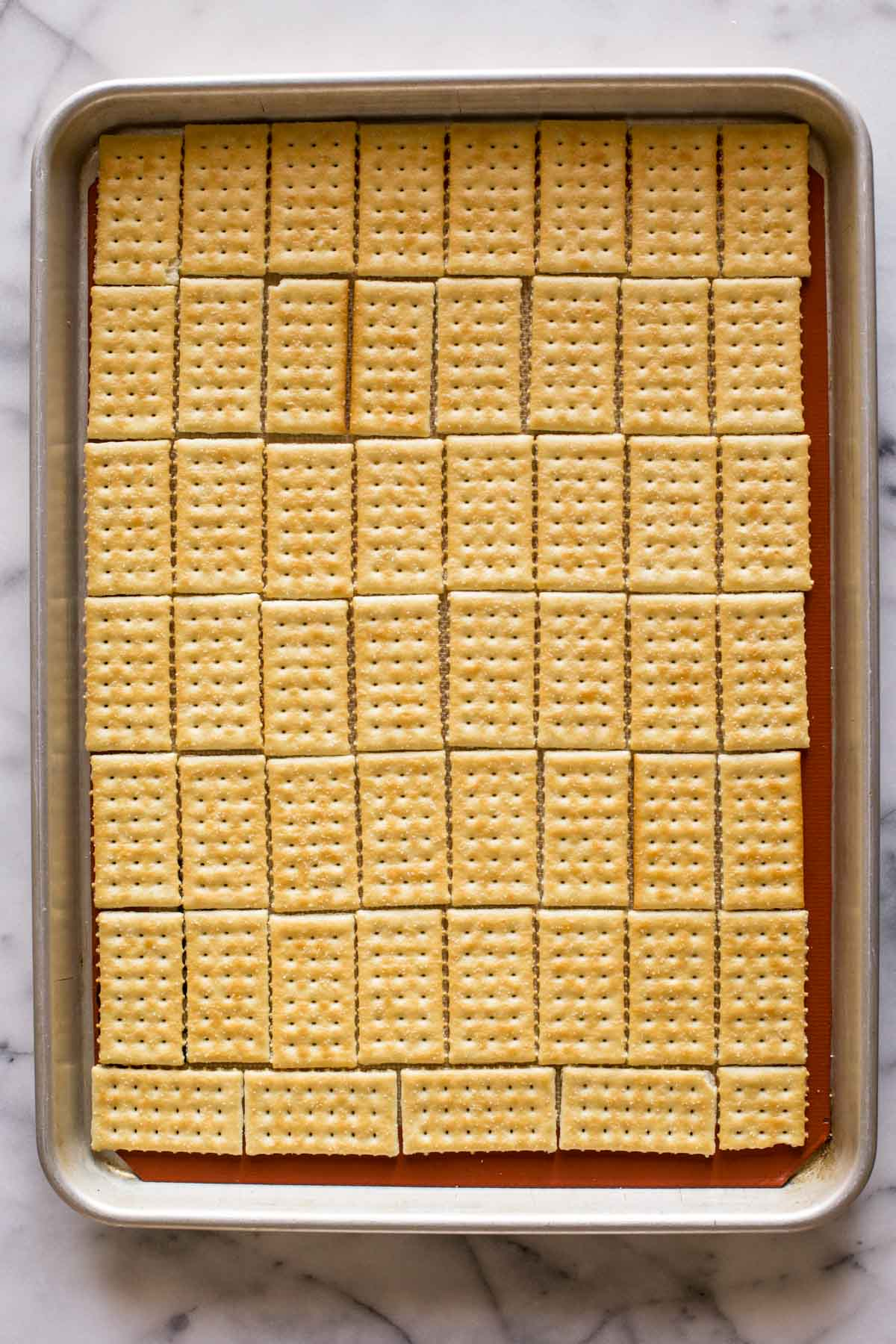 A Silpat lined, rimmed baking sheet with butter crackers arranged in a single layer for the base of the Take Five Cracker Bark.
