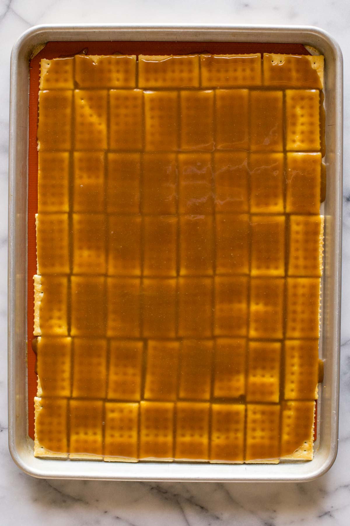 A Silpat lined, rimmed baking sheet with butter crackers arranged in a single layer with the caramel mixture poured on top of them.