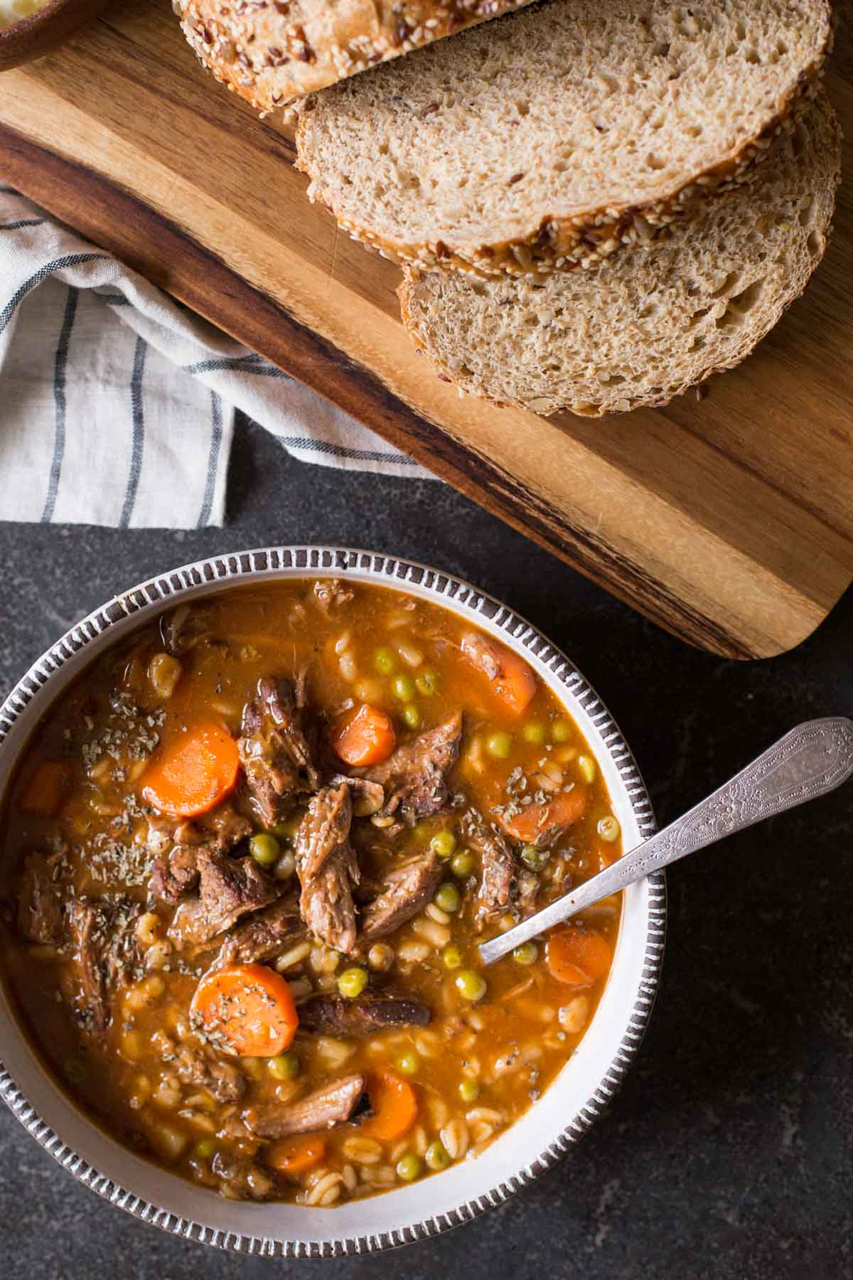 Beef and Barley Vegetable Soup in a bowl with a spoon, sitting next to a cutting board with bread on it.