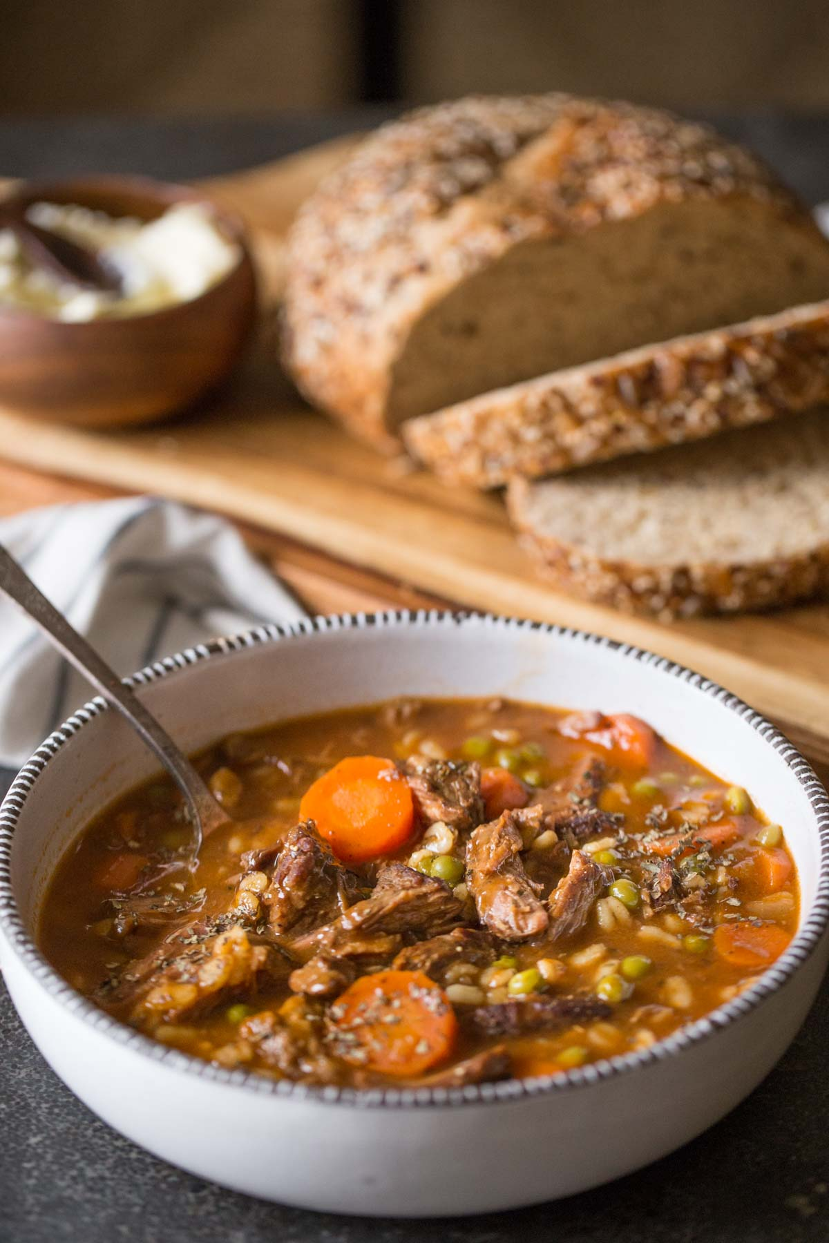 Beef and Barley Vegetable Soup in a bowl with a spoon, sitting next to a cutting board with bread and a small bowl of soft butter.