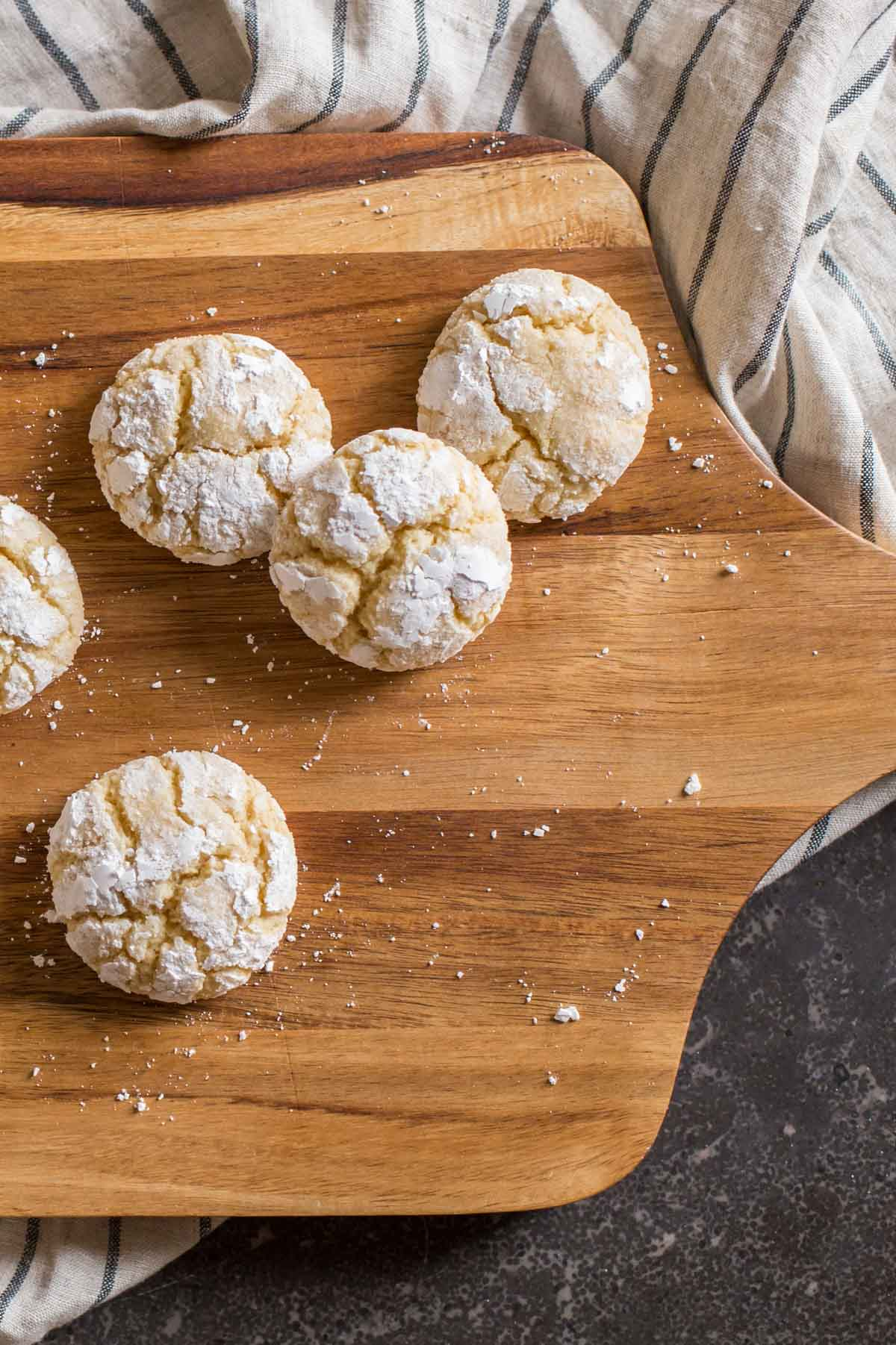 Brown Butter Almond Crinkle Cookies on a wood cutting board.