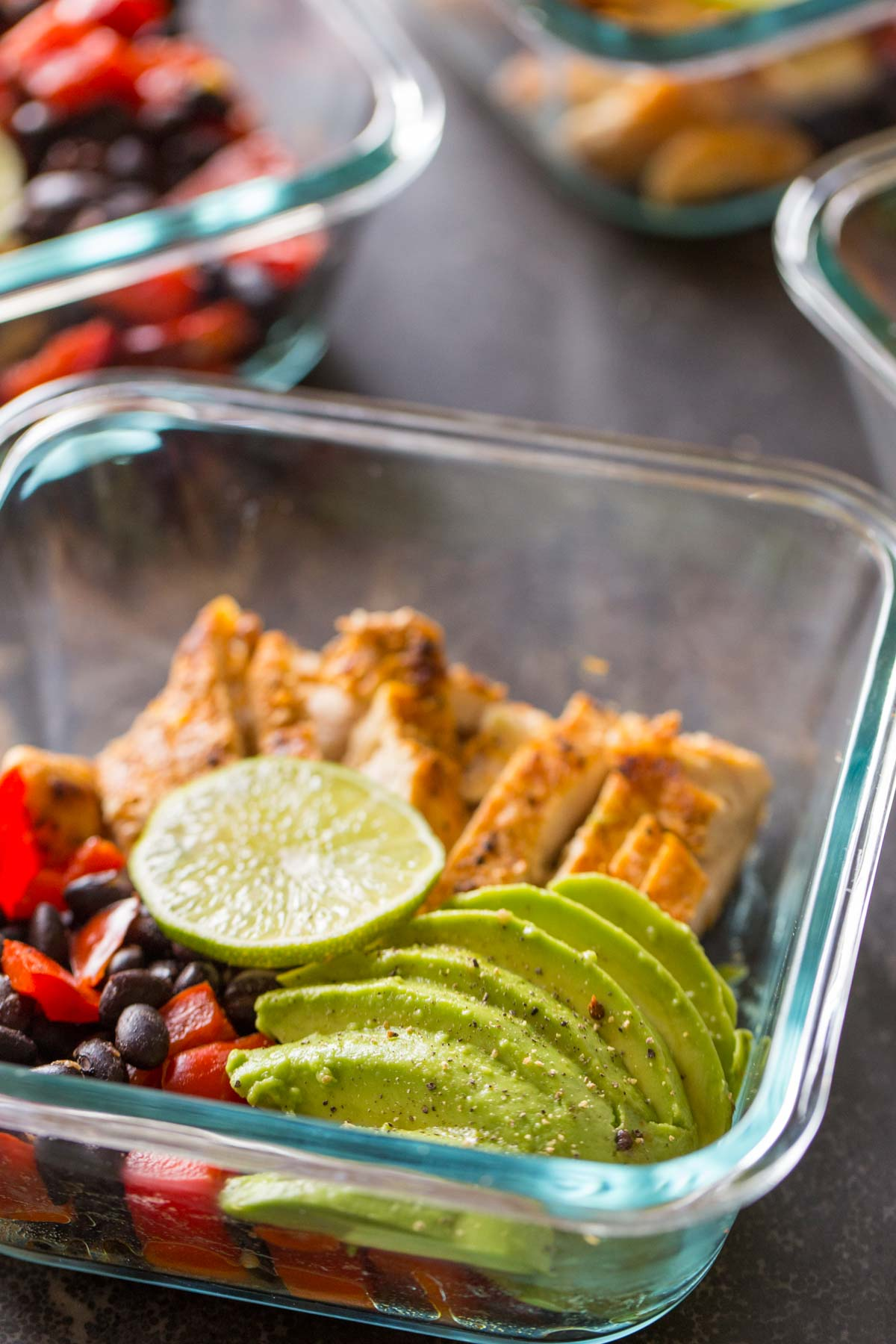 A Healthy Southwestern Chicken Bowl, topped with a slice of lime and some sliced avocado.