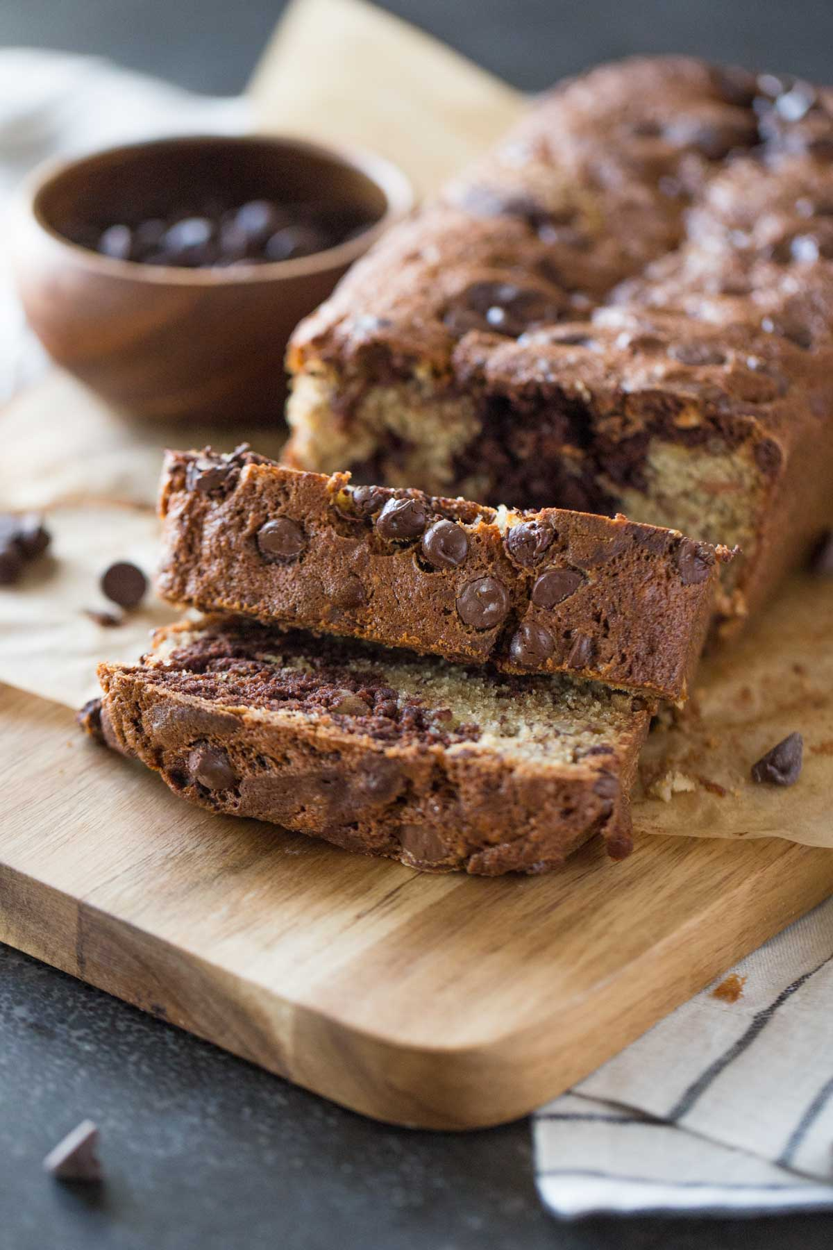 A loaf of Marbled Chocolate Banana Bread on a cutting board with a small wood bowl of chocolate chips.