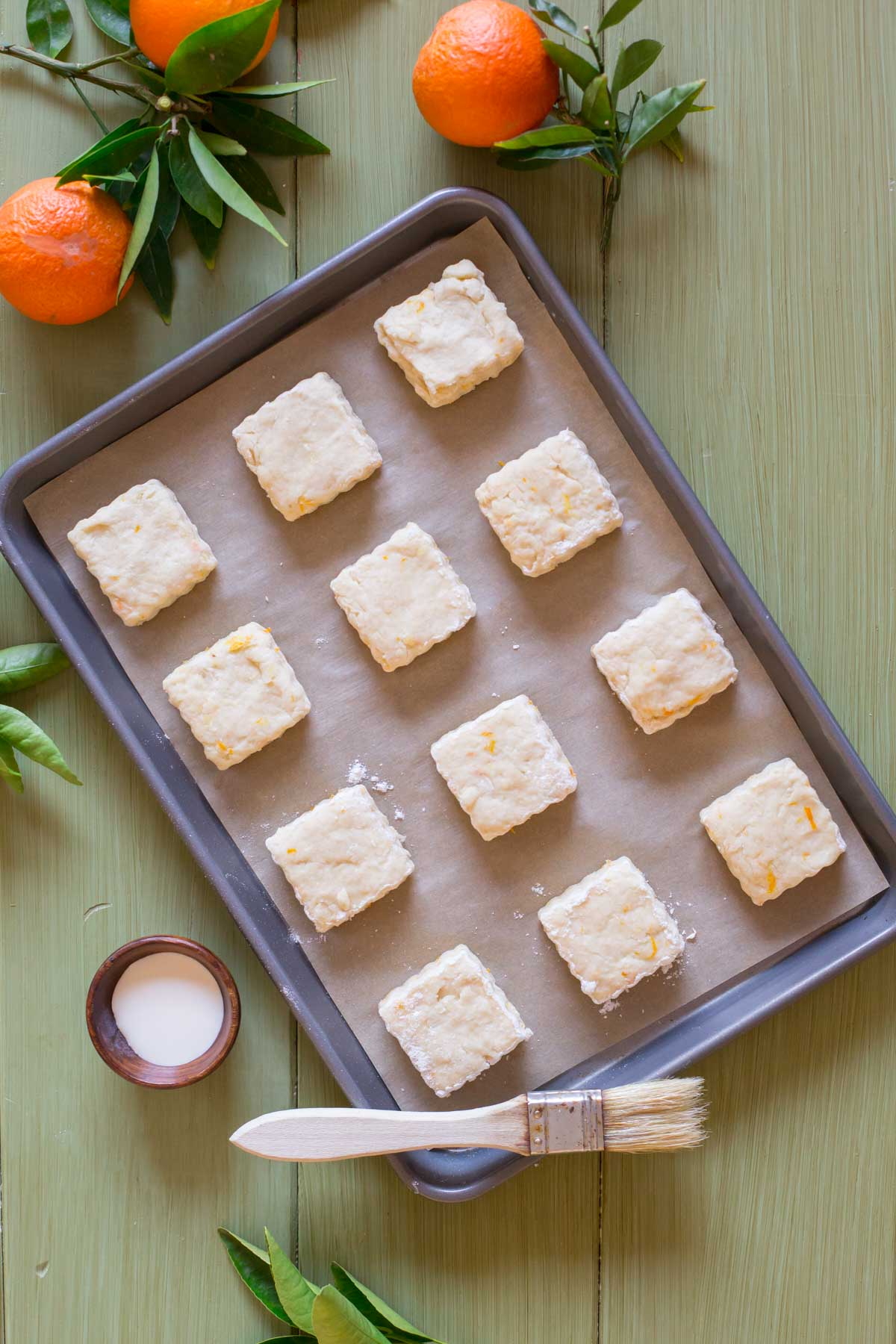 Mini Orange Cream Scones on a parchment paper lined baking sheet, with a small bowl of heavy cream next to it, along with a pastry brush.