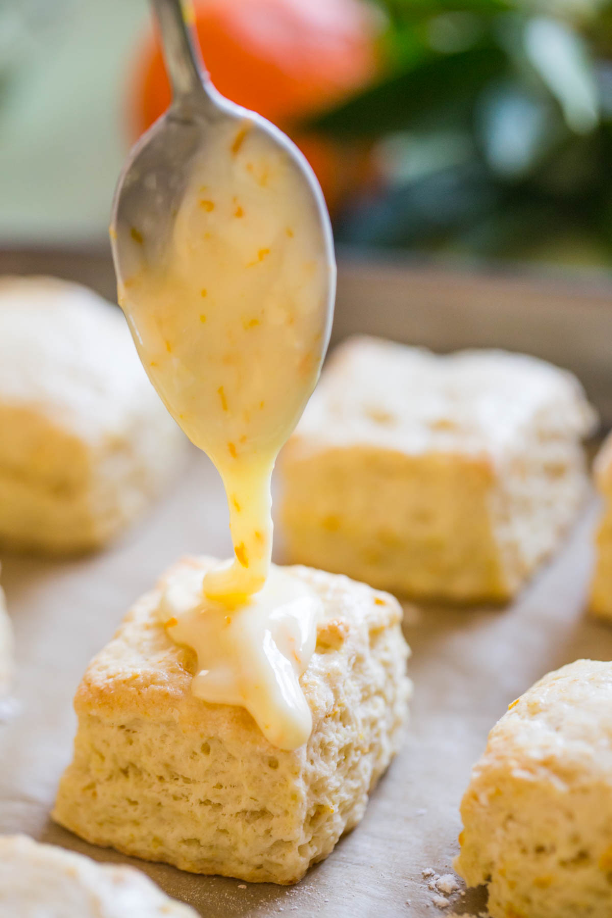 Mini Orange Cream Scones on a parchment paper lined baking sheet, being topped with orange icing.