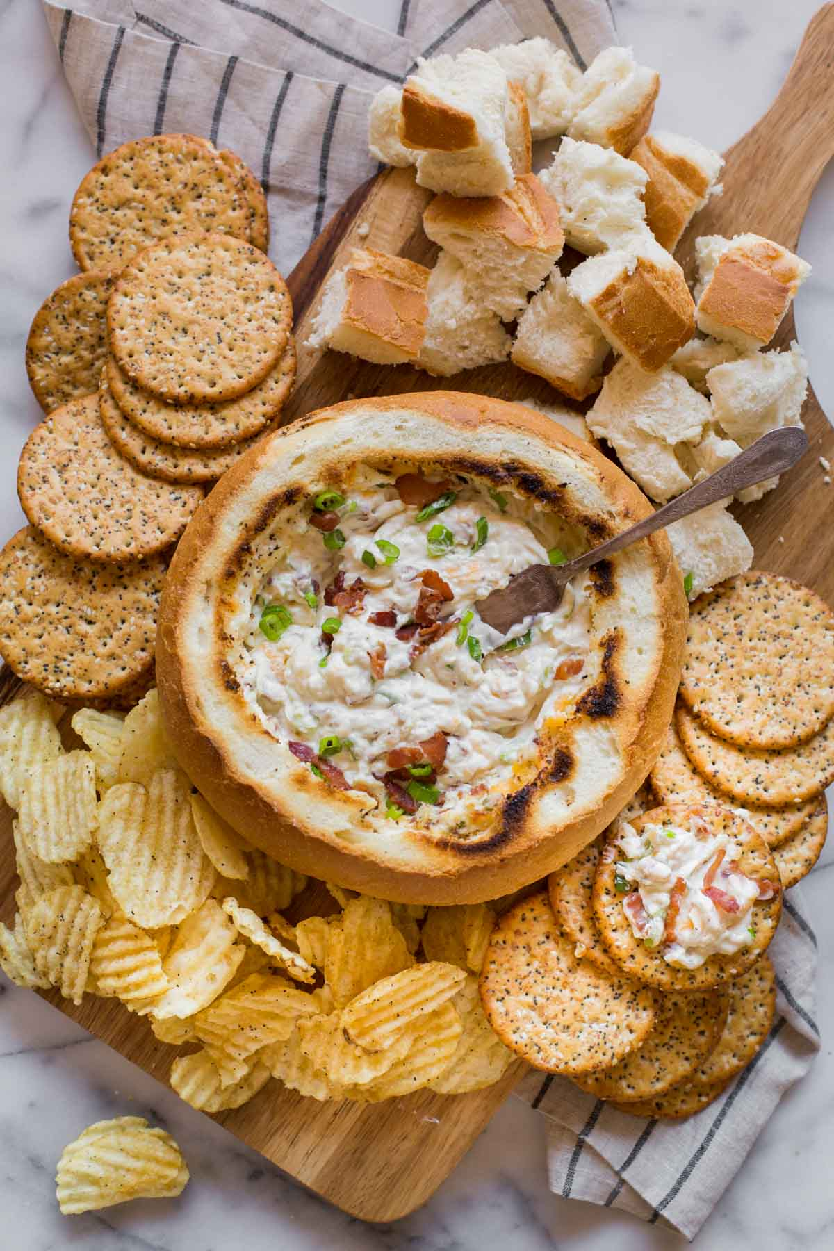 Three Cheese Bacon Dip in a bread bowl sitting on a wood board, surrounded by bread chunks, chips and crackers.