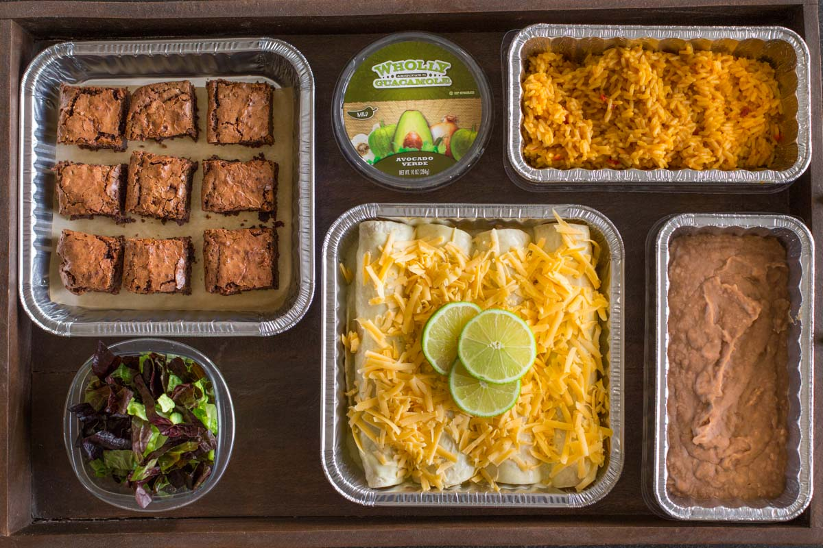 A wood tray with a pan of Honey Lime Chicken Enchiladas before being cooked, a pan of Healthy Crockpot Refried Beans, a pan of Spanish Rice, a container of Wholly Guacamole, a side salad, and a pan of Extra Thick and Fudgy Homemade Brownies.