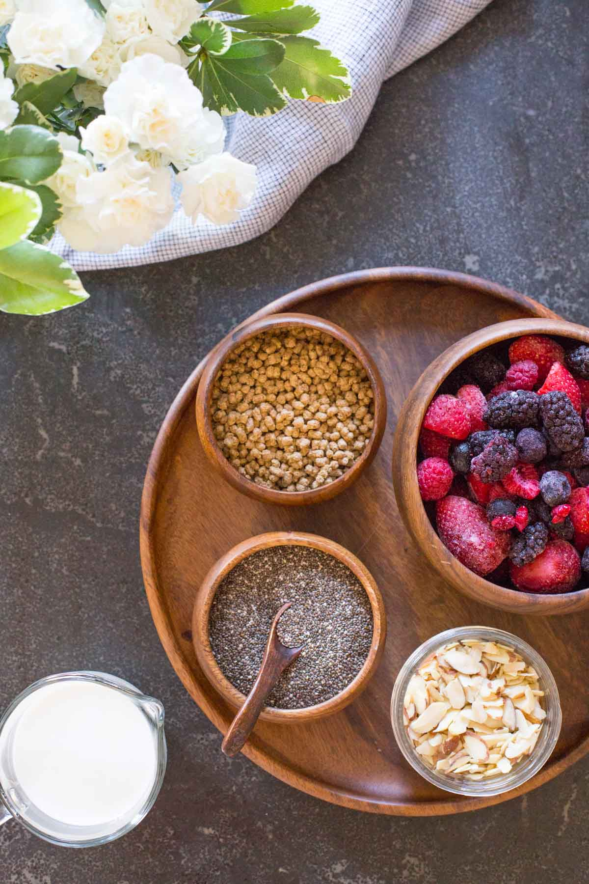 All the ingredients for the Chia Pudding Parfaits - A wood plate with a small wood bowl of bran nuggets, a small wood bowl of chia seeds, a small glass dish of sliced almonds, and a wood bowl of frozen mixed berries, sitting next to a small pour cup of milk.
