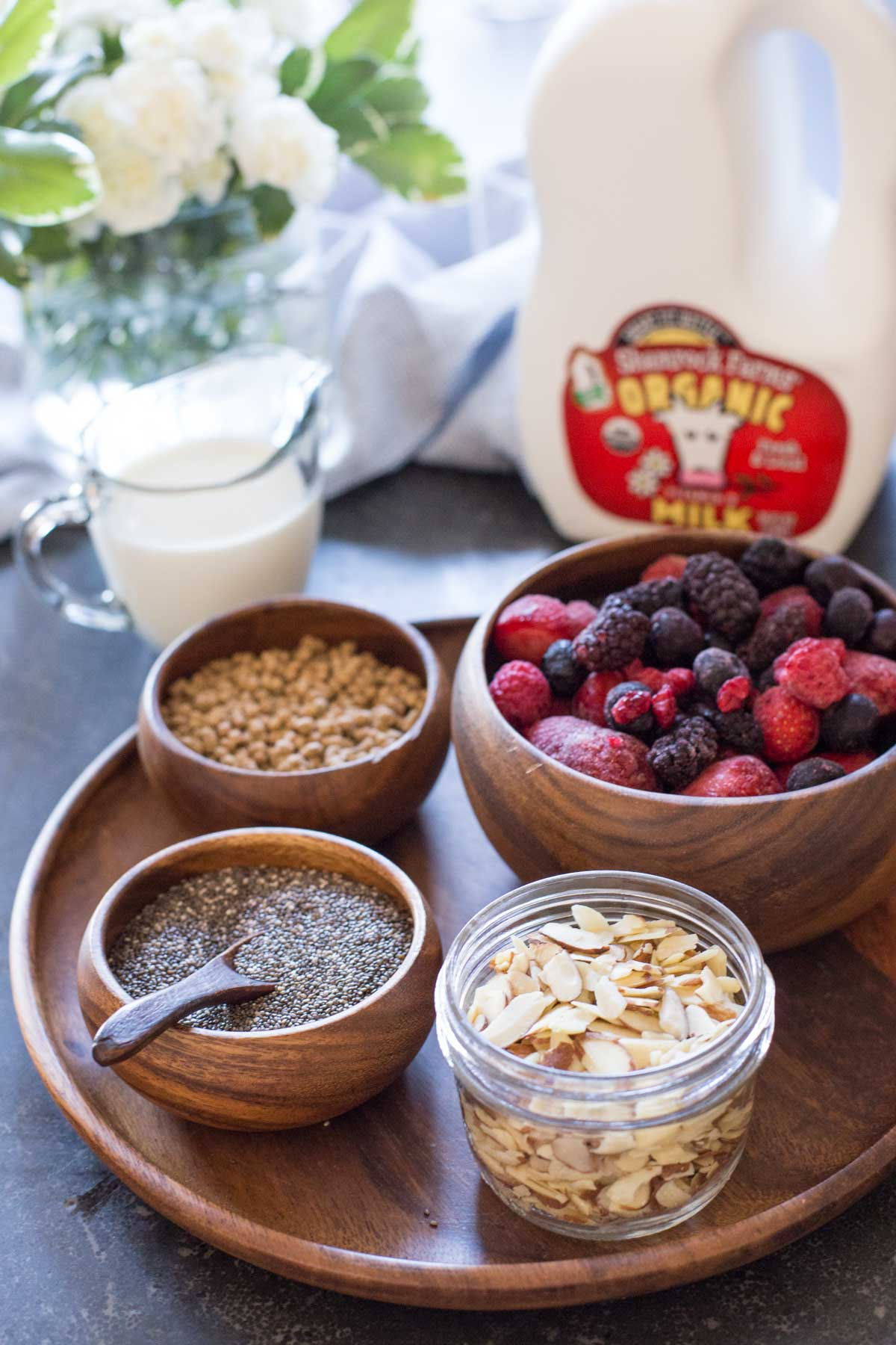 All the ingredients for the Chia Pudding Parfaits - A wood plate with a small wood bowl of bran nuggets, a small wood bowl of chia seeds, a small glass dish of sliced almonds, and a wood bowl of frozen mixed berries, sitting next to a milk jug and a small pour cup of milk.