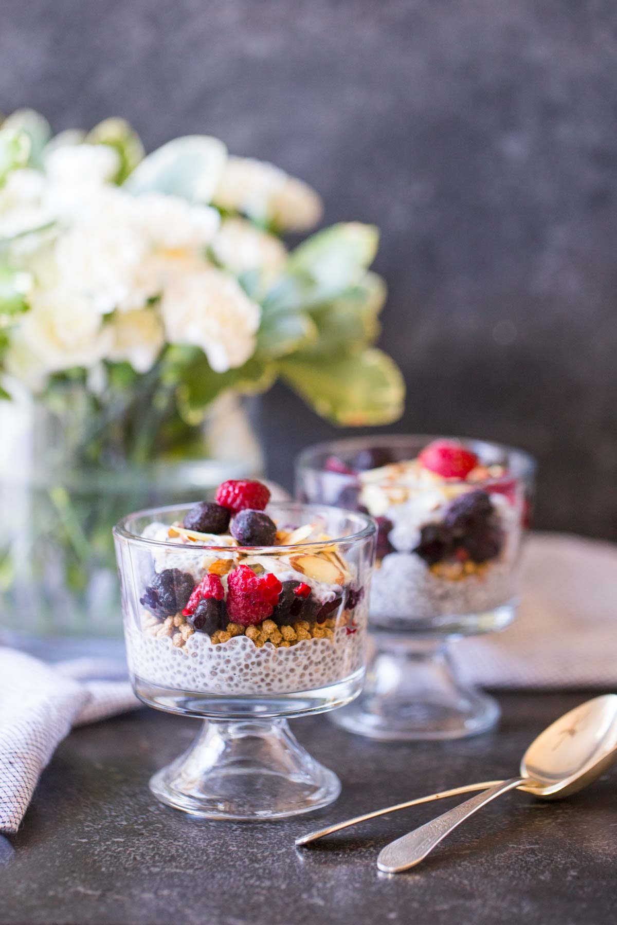 Chia Pudding Parfaits assembled in two small glass dishes, with two spoons next to them and a flower arrangement in the background.