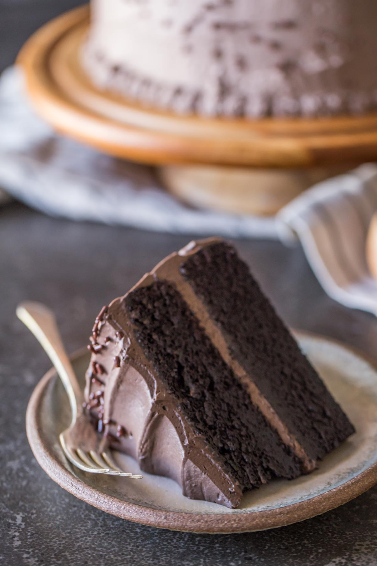 A slice of Dark Chocolate Cake With Whipped Cream Frosting on a plate with a fork, and the rest of the cake on a cake stand in the background.