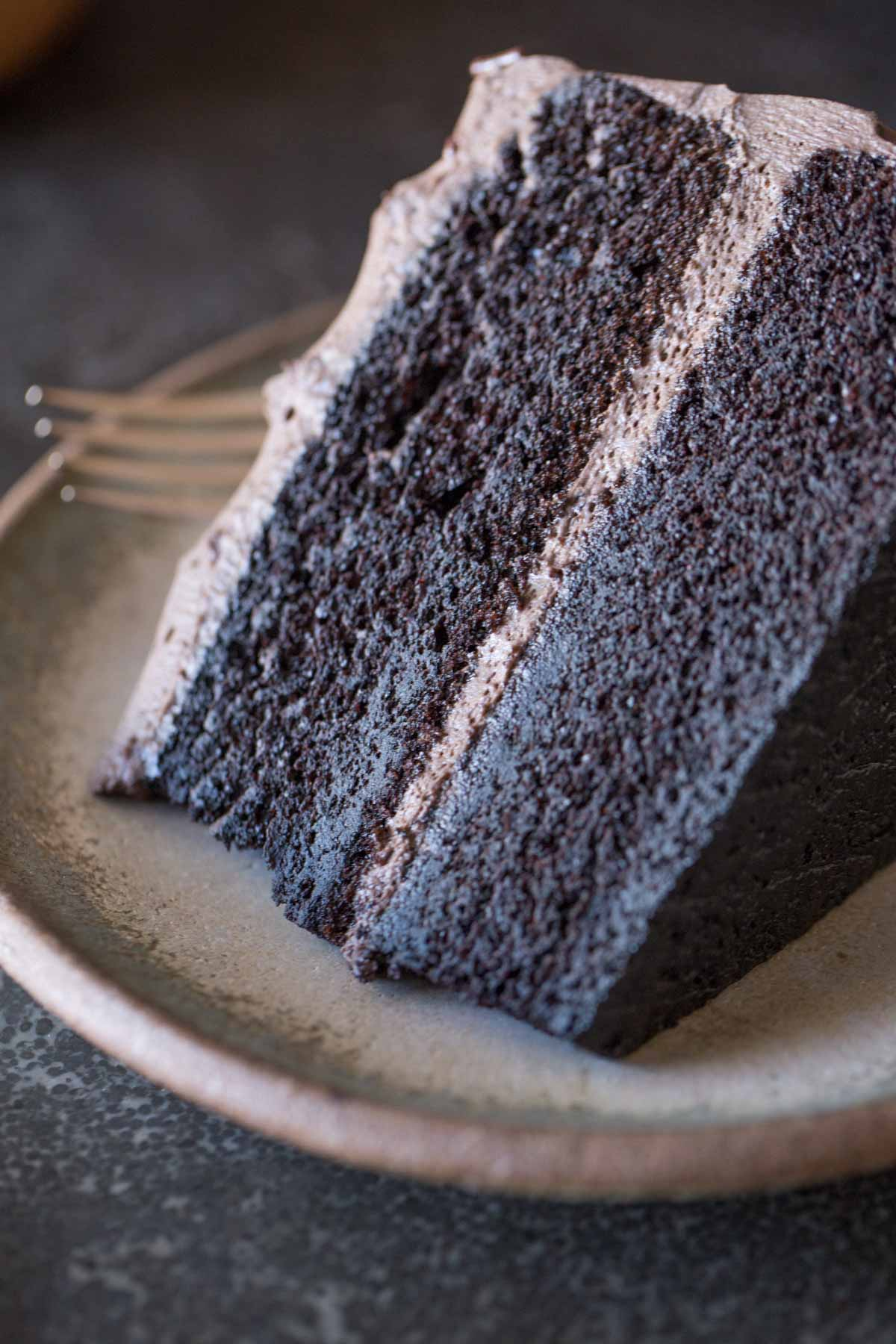 A slice of Dark Chocolate Cake With Whipped Cream Frosting on a plate with a fork.