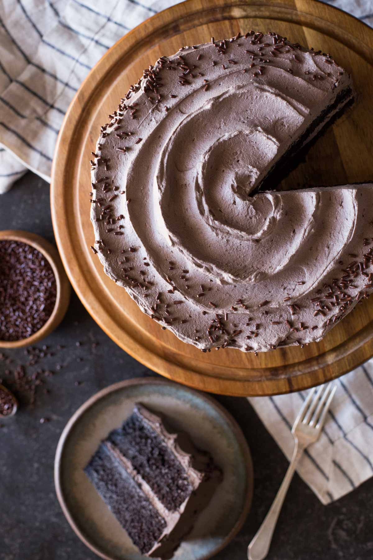 A slice of Dark Chocolate Cake With Whipped Cream Frosting on a plate, sitting next to the rest of the cake on a cake stand and a small wood bowl of chocolate sprinkles.