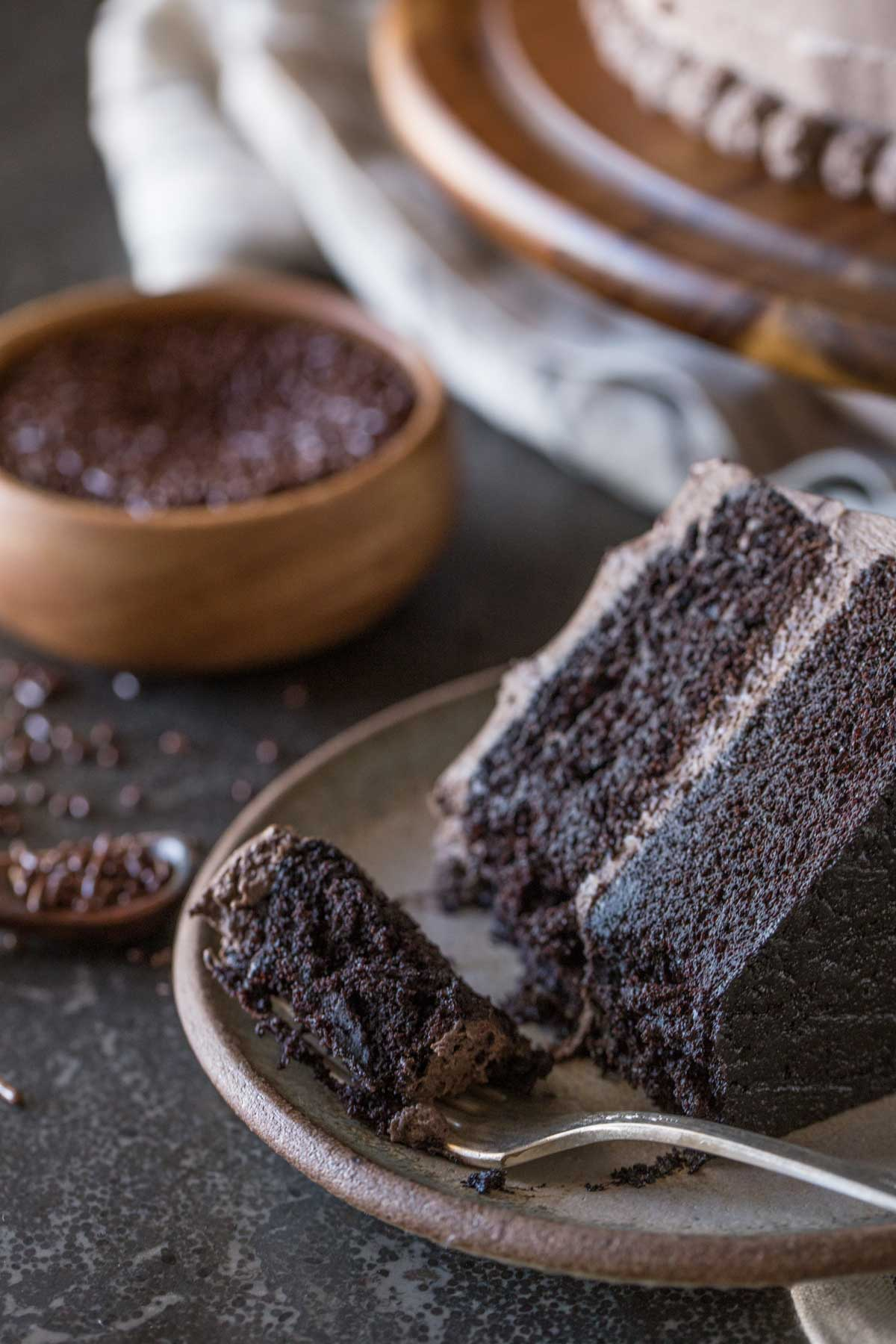 A slice of Dark Chocolate Cake With Whipped Cream Frosting on a plate along with a fork full of cake, and a small wood bowl of chocolate sprinkles in the background.
