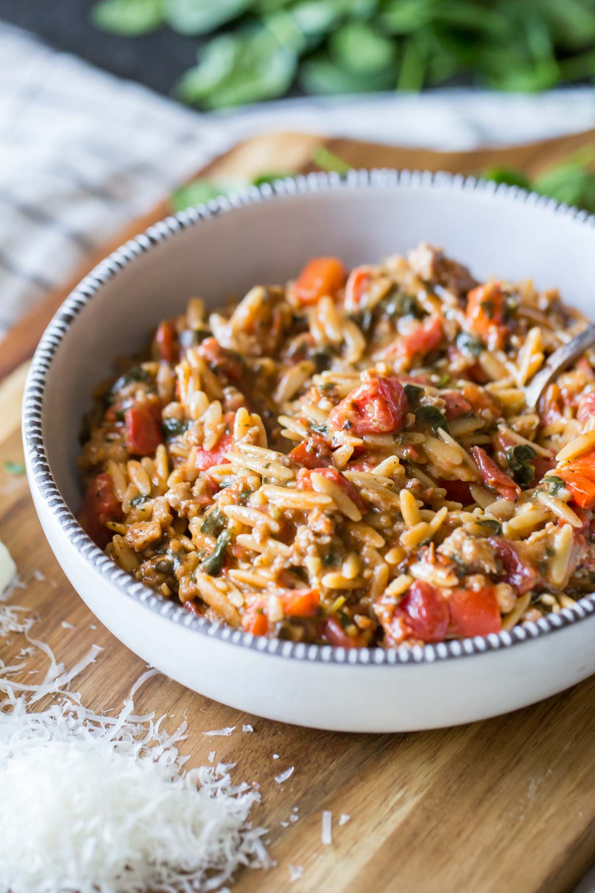 One Pot Creamy Tomato Orzo in a bowl, sitting on a board with some freshly grated parmesan cheese and some baby spinach.