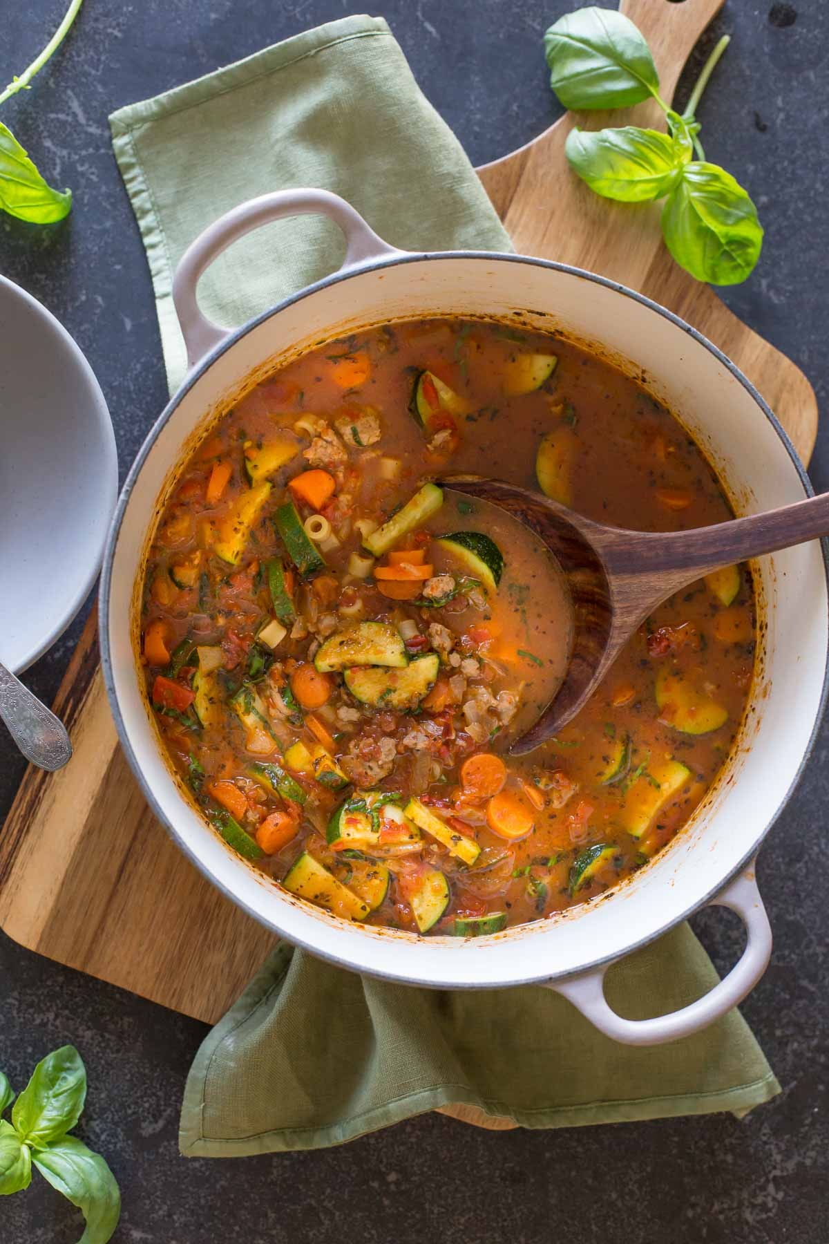 Turkey and Vegetable Ditalini Soup in a large pot with a wood serving spoon in it.