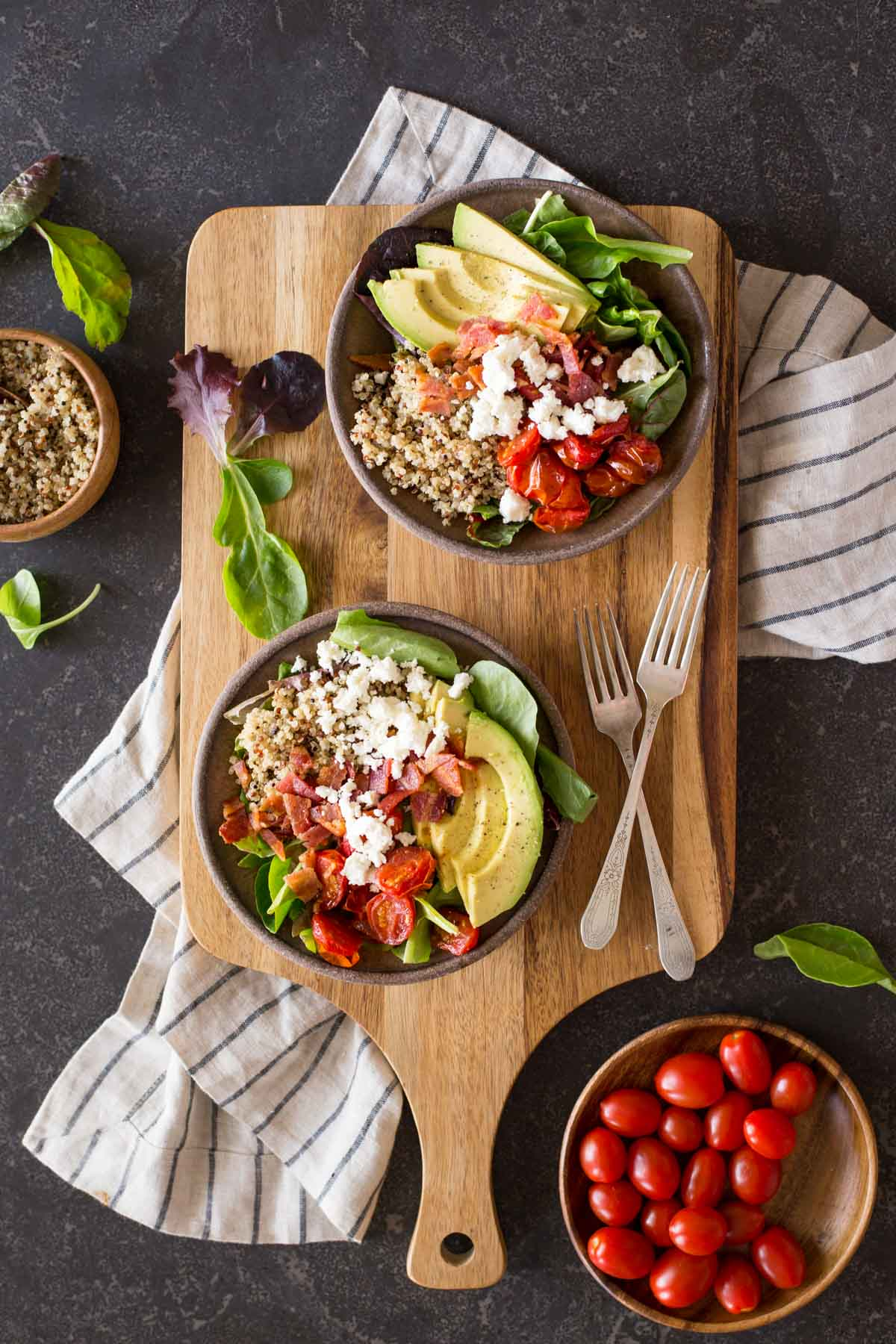 Two BLT Bliss Bowls on a cutting board with two forks, with a bowl of grape tomatoes and a bowl of quinoa next to the board.