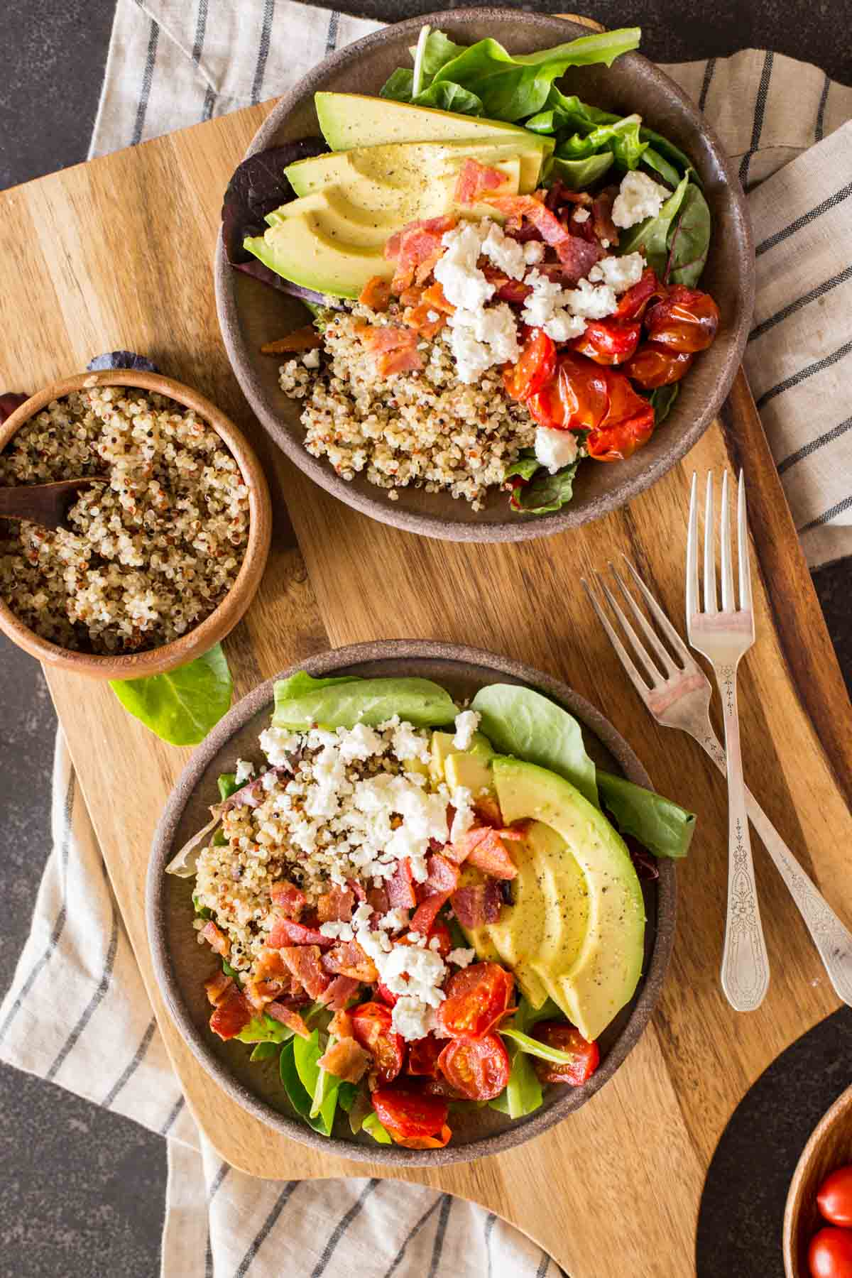 Two BLT Bliss Bowls on a cutting board with two forks, along with a bowl of quinoa.
