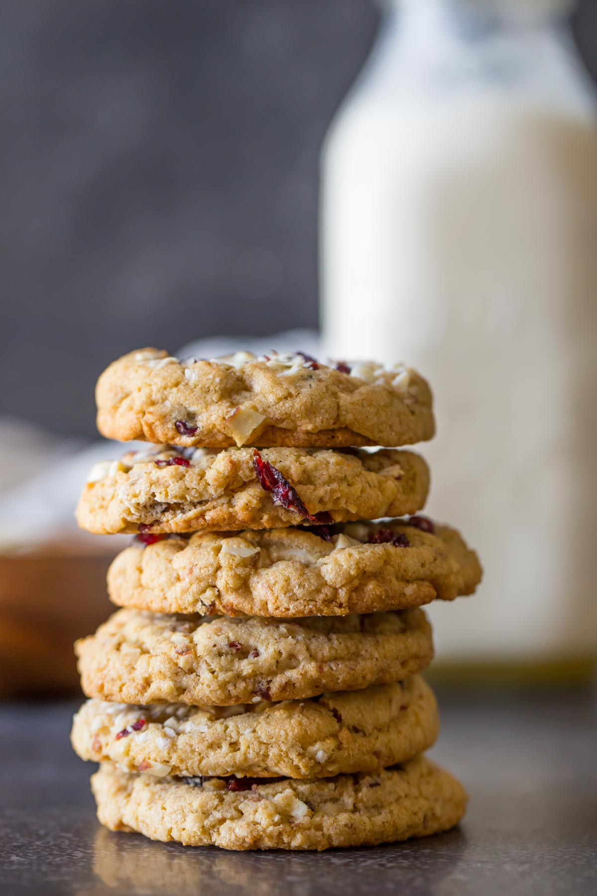 Cranberry Almond White Chocolate Chunk Cookies stacked in a pile of six, with a glass jar of milk in the background.