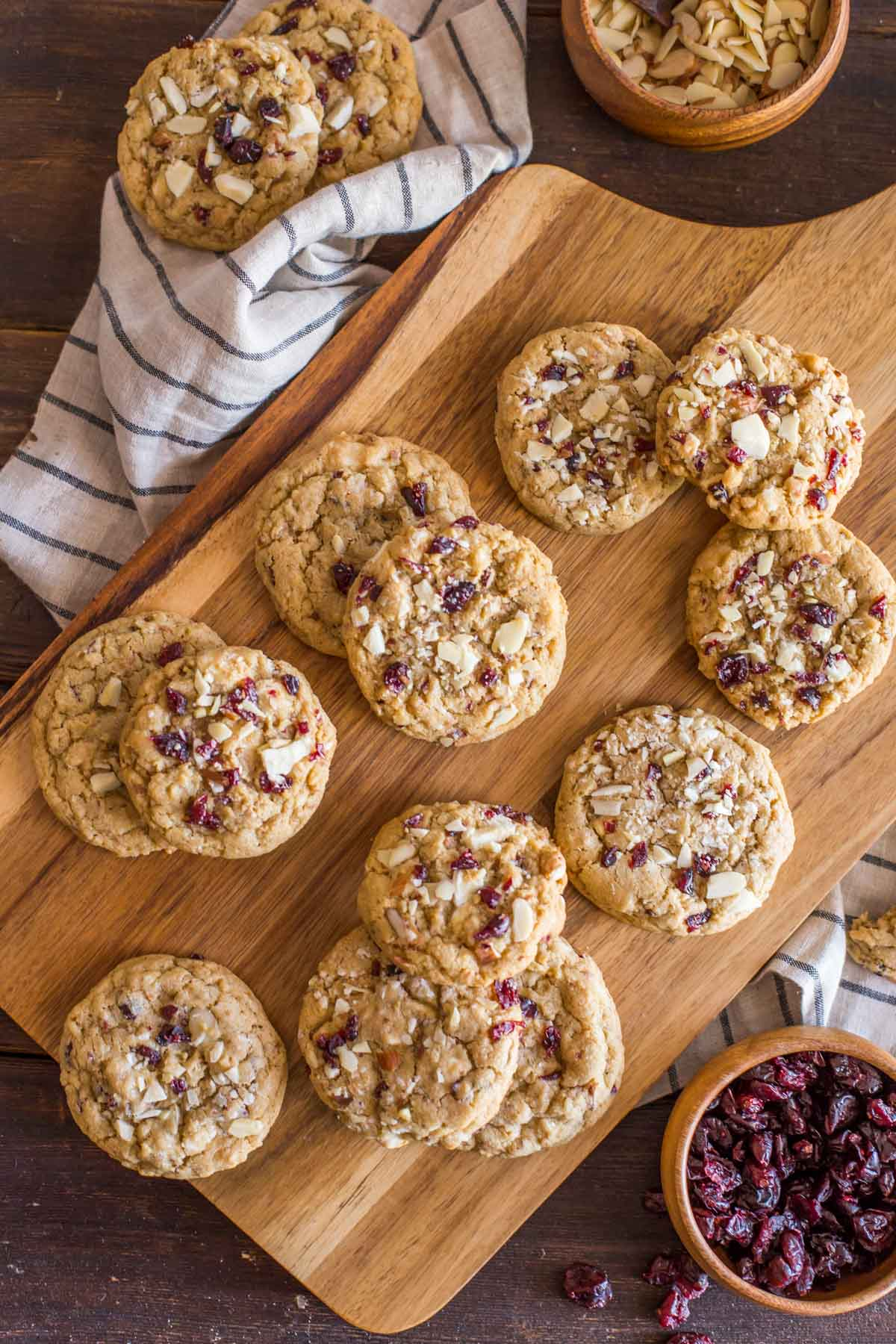 Cranberry Almond White Chocolate Chunk Cookies on a wood cutting board, with a wood bowl of sliced almonds and a wood bowl of dried cranberries next to the board.