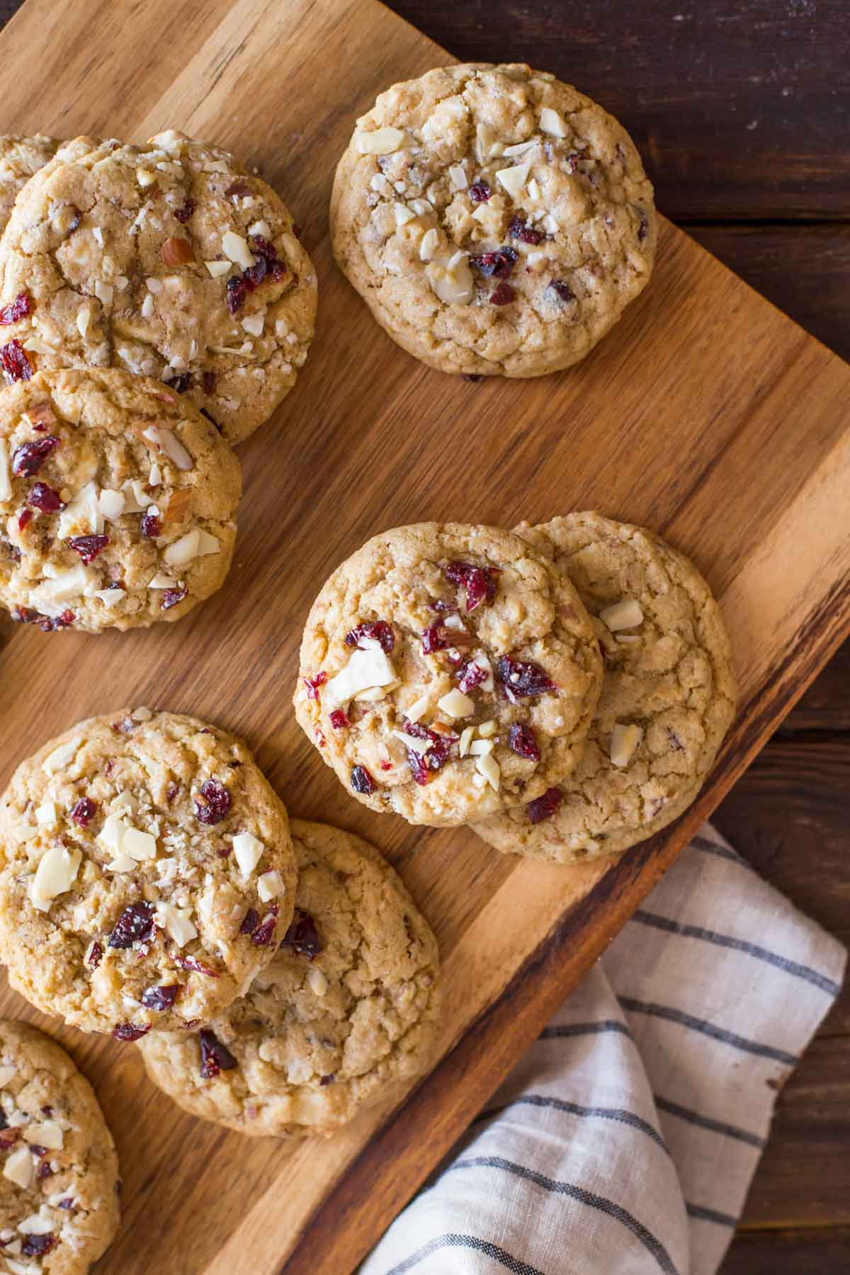 Cranberry Almond White Chocolate Chunk Cookies on a wood cutting board.
