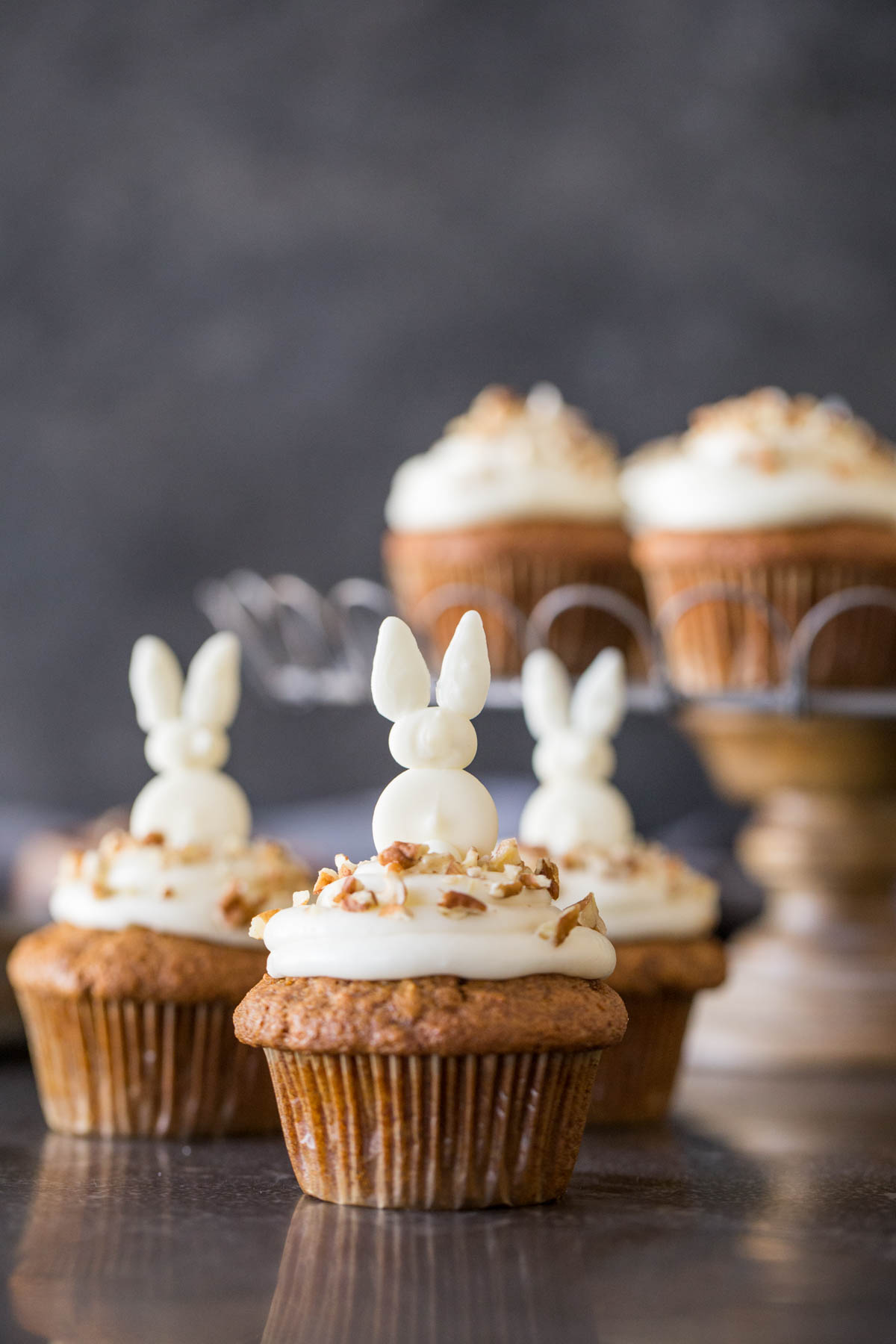 Three Carrot Cake Cupcakes with white chocolate bunnies on top, and more cupcakes on a cake stand in the background.