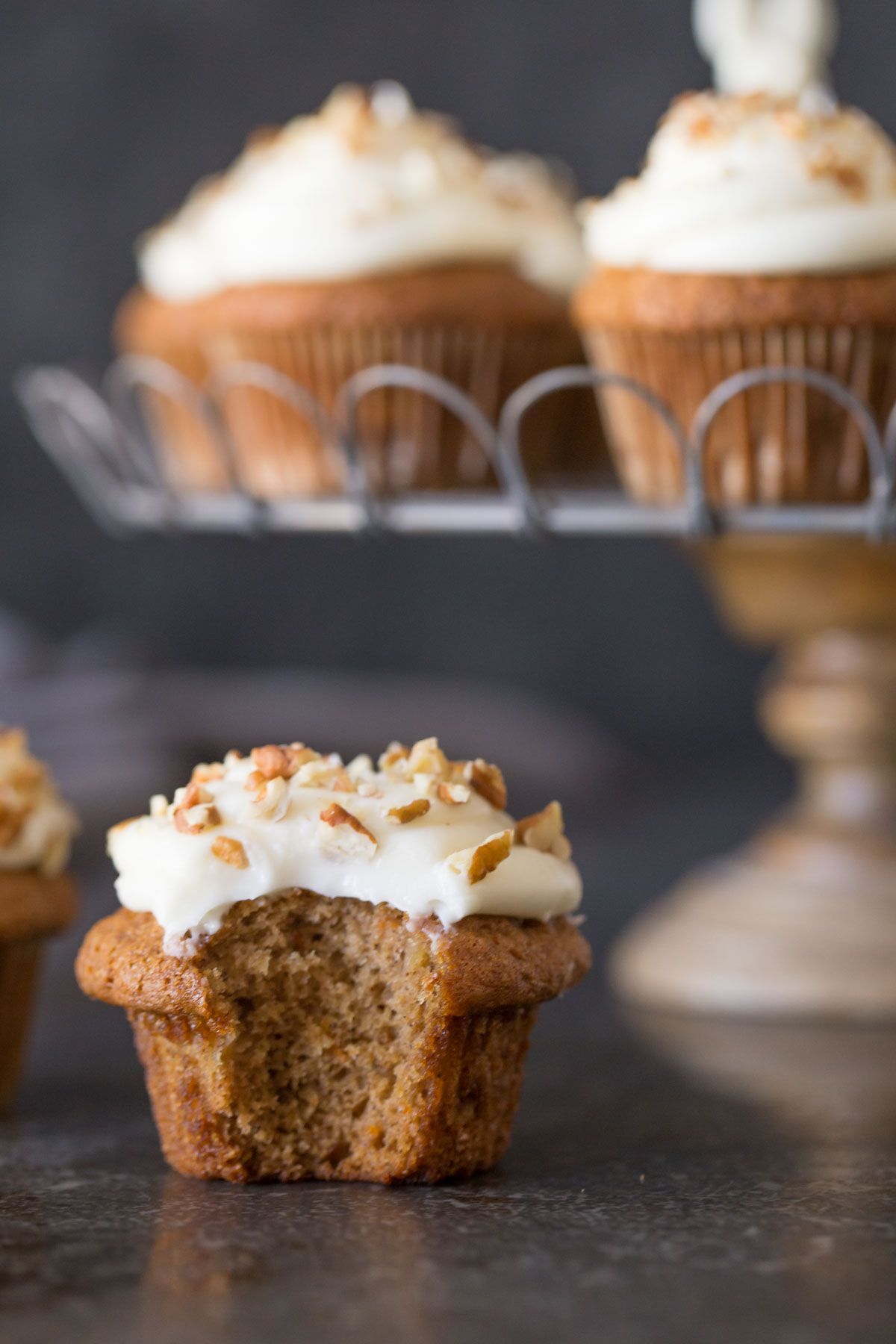 A Carrot Cake Cupcake with a bite taken out of it, with more Carrot Cake Cupcakes on a cake stand in the background.