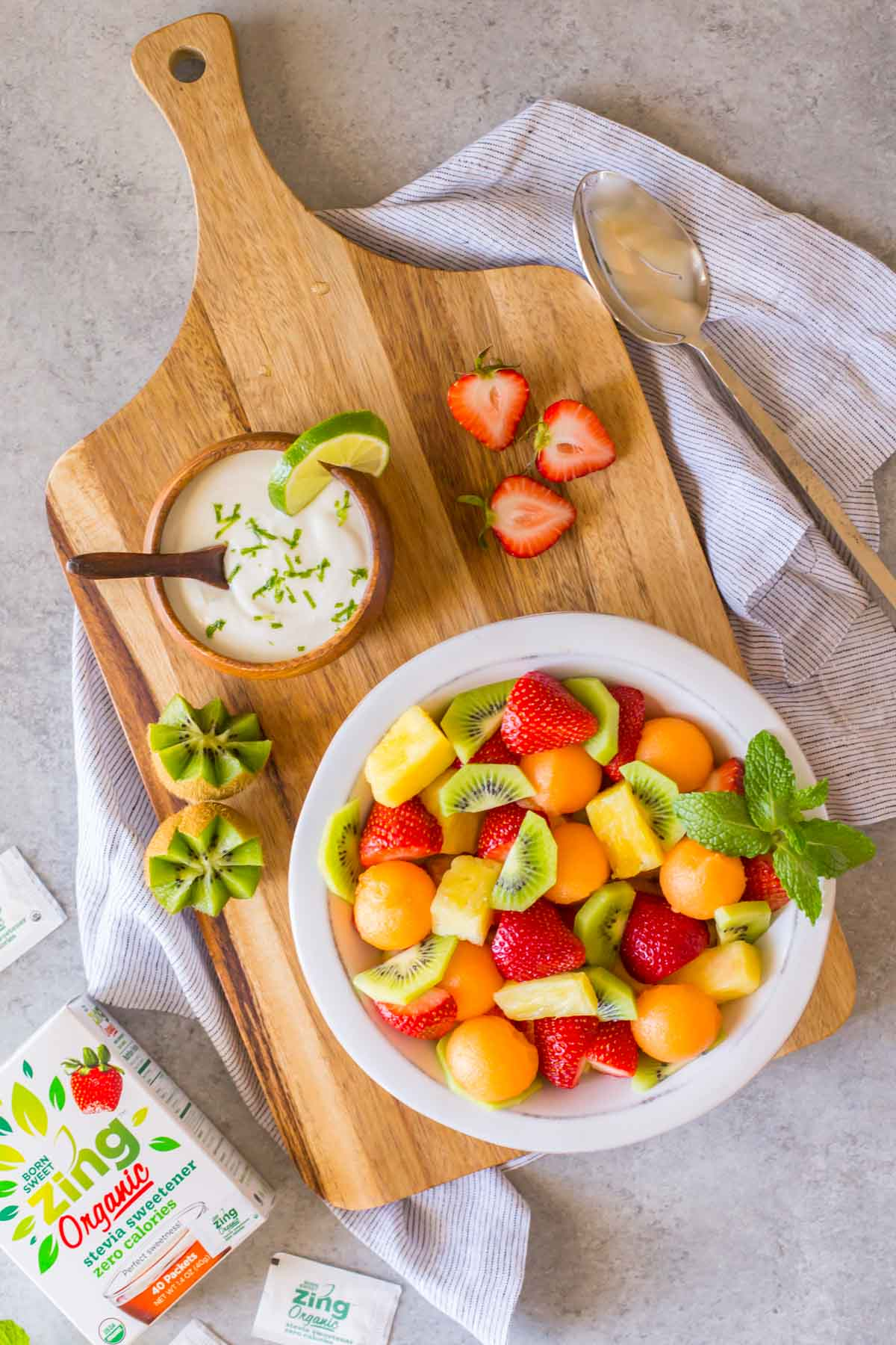 A bowl of Summer Fruit Salad sitting on a cutting board along with a small bowl of Coconut Lime Yogurt and some strawberries and kiwis, with a box of Born Sweet Zing Organic Stevia Sweetener next to the board.