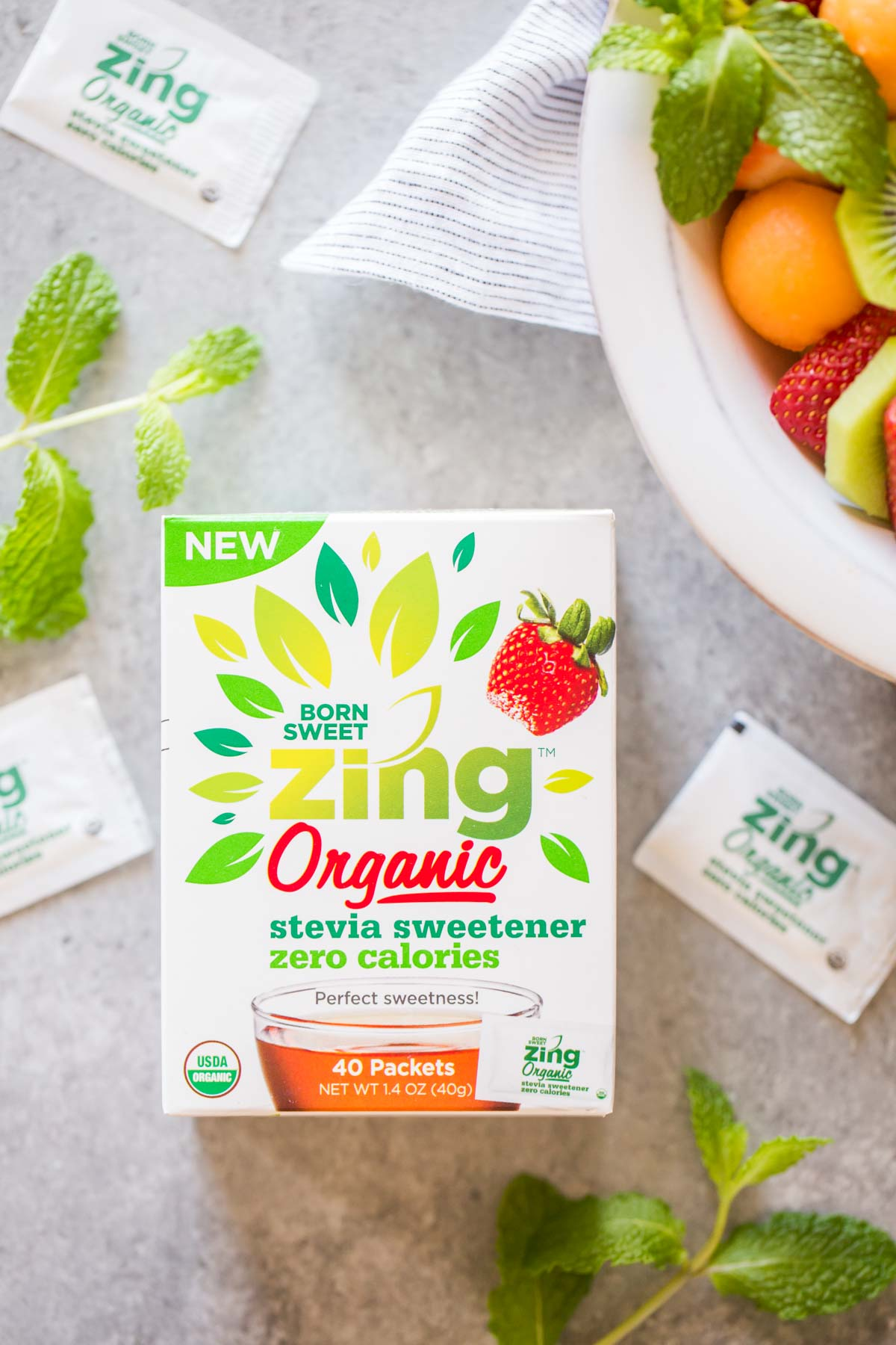 A box of Born Sweet Zing Organic Stevia Sweetener, sitting next to the bowl of Summer Fruit Salad.