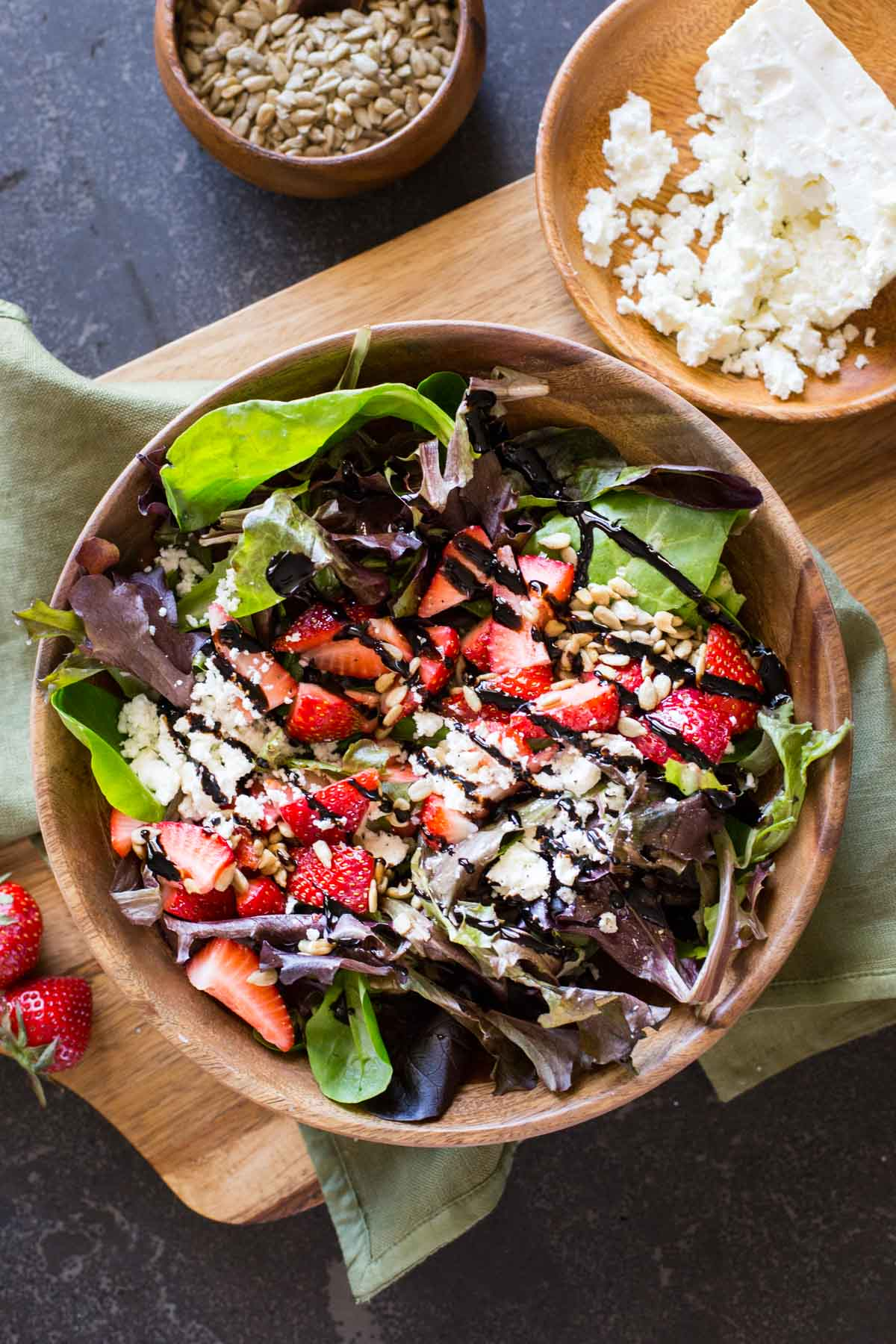 A bowl of Easy Strawberry Balsamic Salad sitting next to a small bowl of crumbled feta and a small bowl of sunflower seeds.