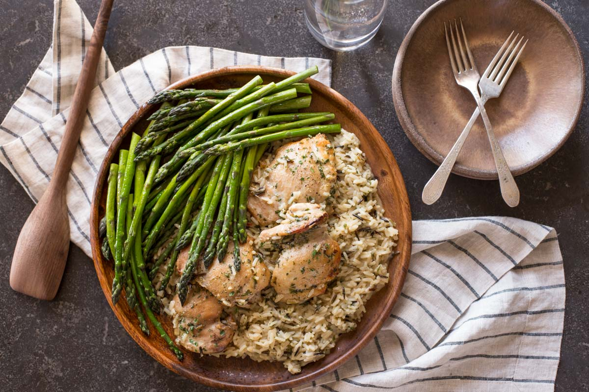 One Pot Chicken and Rice Dinner on a large serving plate, sitting next to some plates, forks, a glass and a wooden spoon.