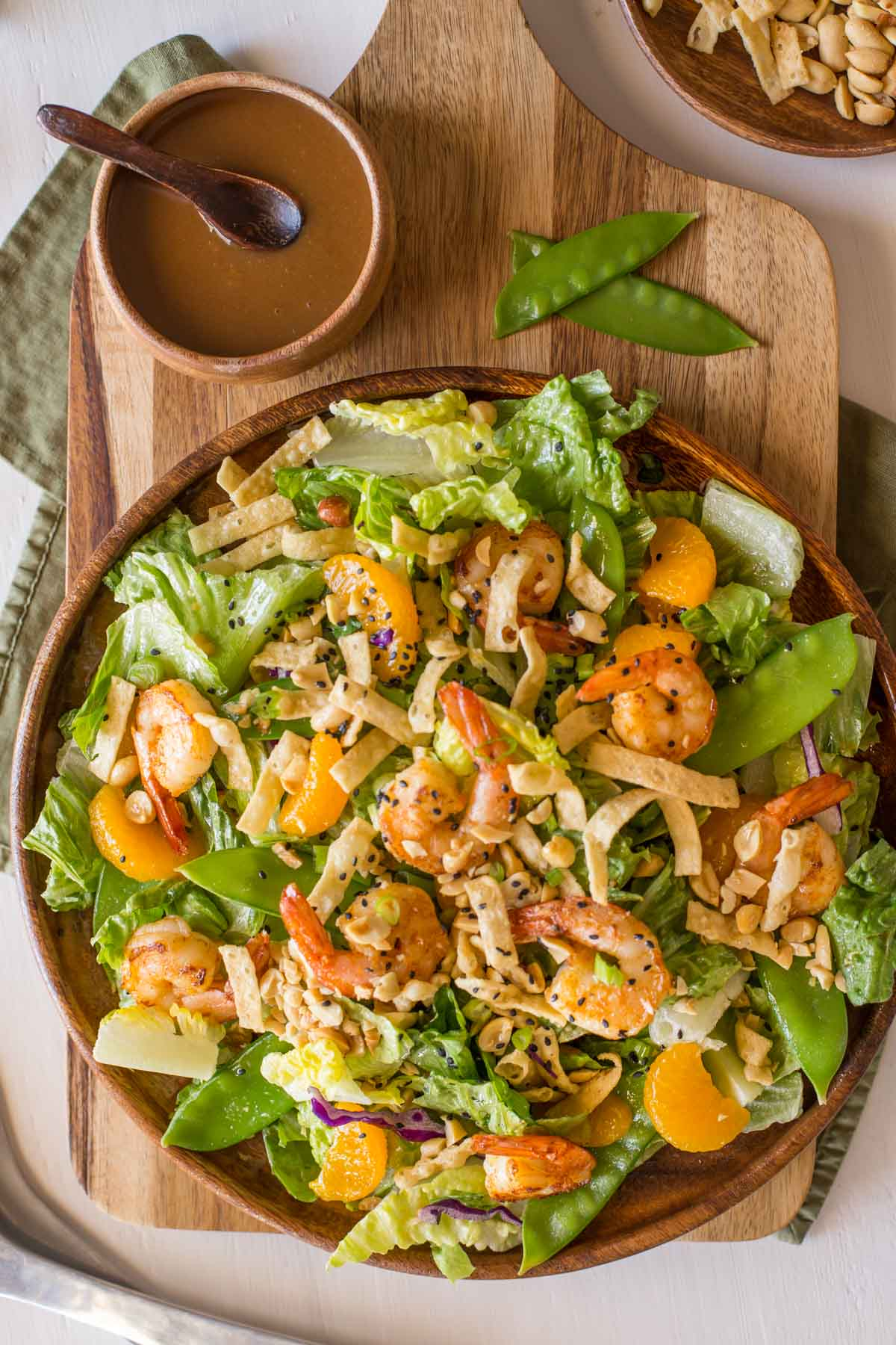 Shrimp Salad on a large serving plate, sitting next to a small wood bowl of the Spicy Peanut Dressing and a bowl of crispy wonton strips and peanuts.