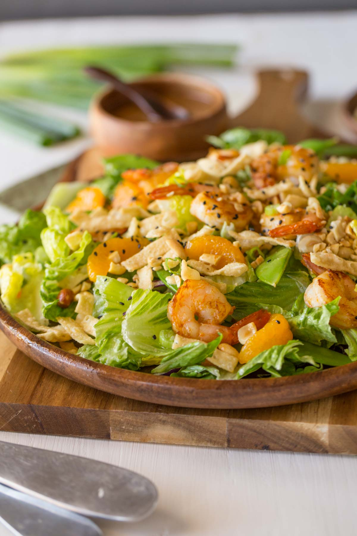 Shrimp Salad on a large serving plate, with a small wood bowl of the Spicy Peanut Dressing in the background.