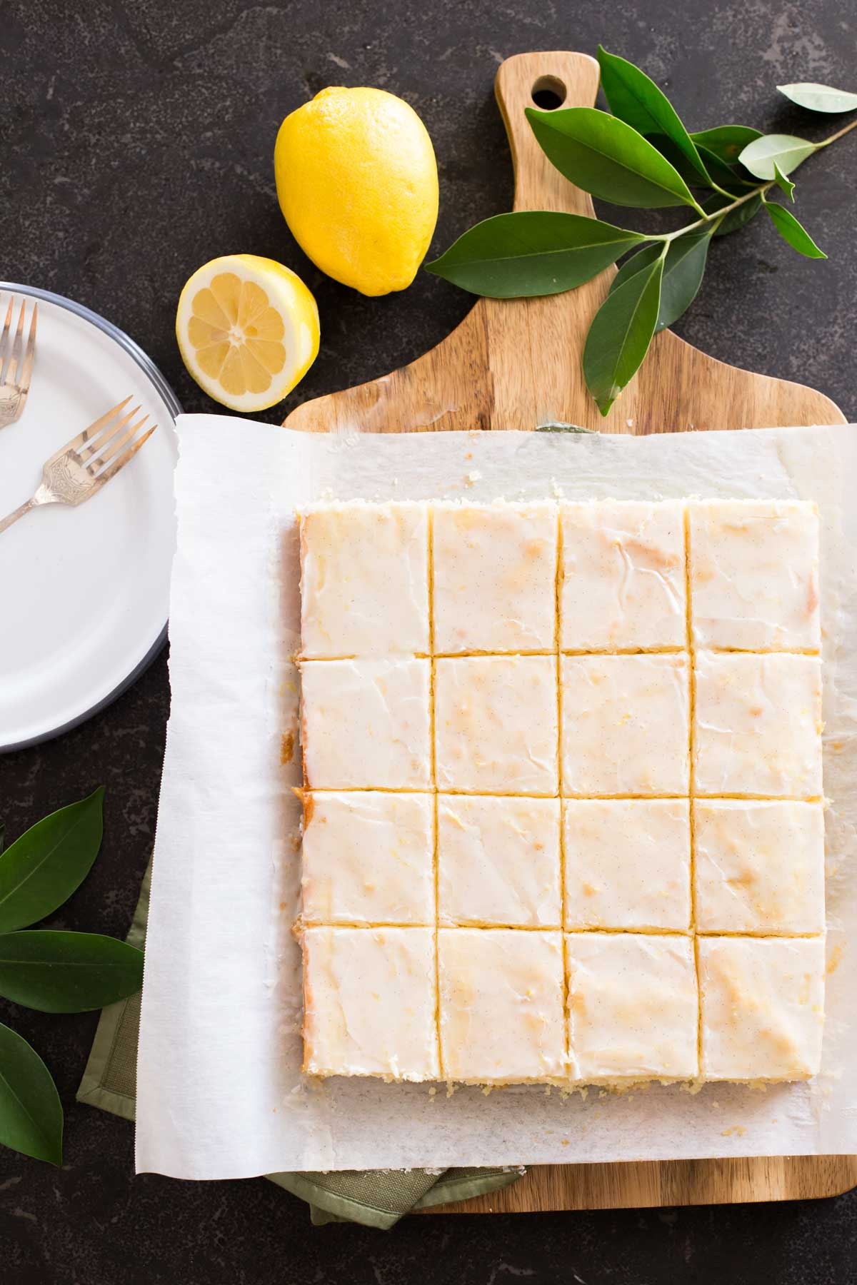 Vanilla Bean Lemon Bars cut into squares on parchment paper on top of a cutting board, with lemons and tree leaves next to the board, along with some plates and forks.