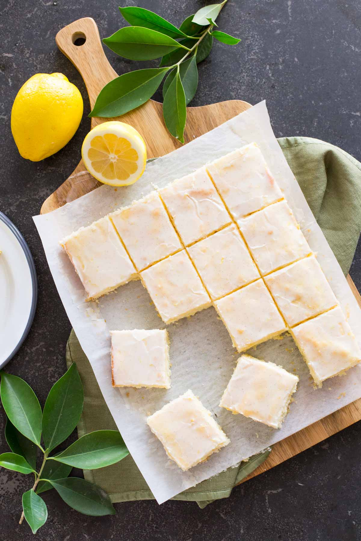 Vanilla Bean Lemon Bars cut into squares on parchment paper on top of a cutting board, with lemons and tree leaves next to the board.