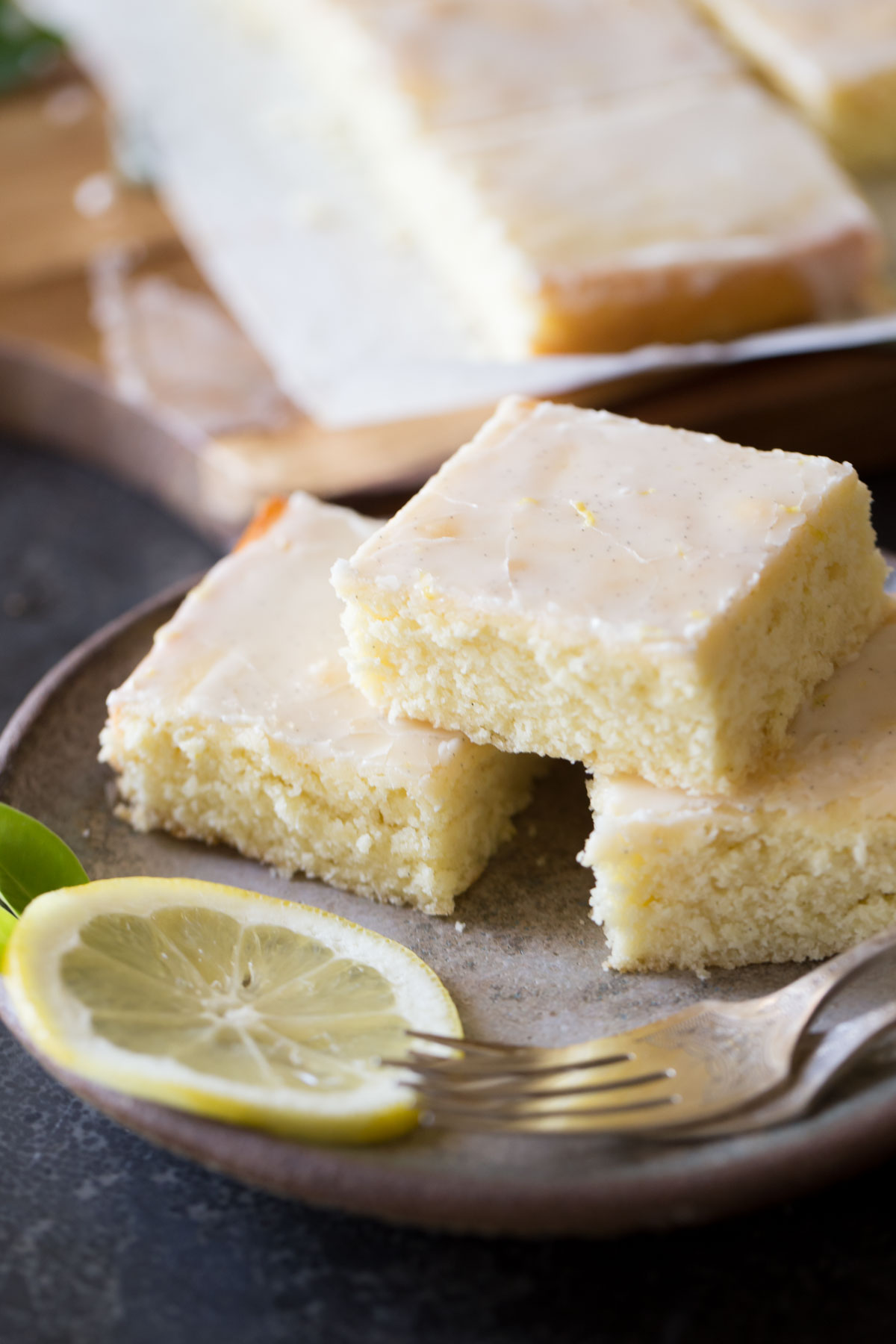 Three Vanilla Bean Lemon Bars on a plate with two forks and a lemon slice, with more Vanilla Bean Lemon Bars in the background.