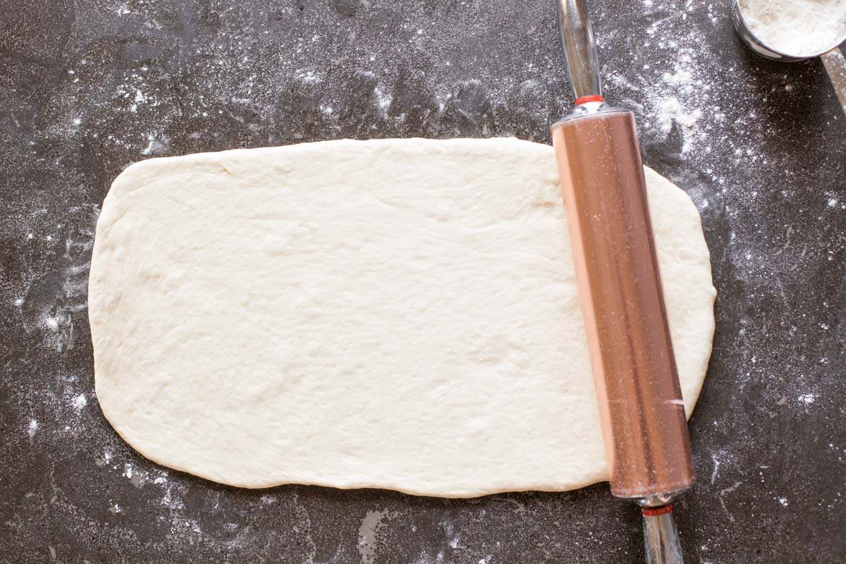 Fresh Buttery Garlic Breadsticks dough rolled out with rolling pin.