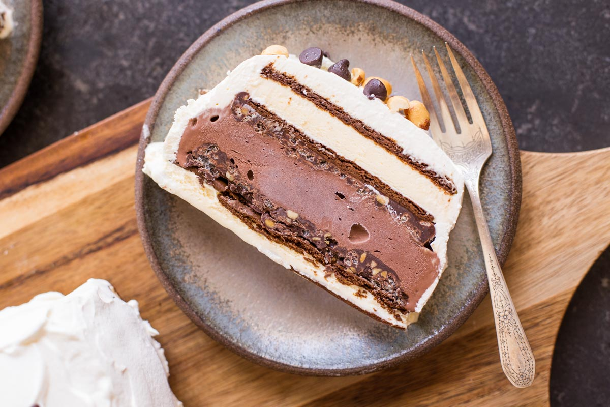 A slice of Chocolate Peanut Butter Ice Cream Slice Cake on a plate with a fork.
