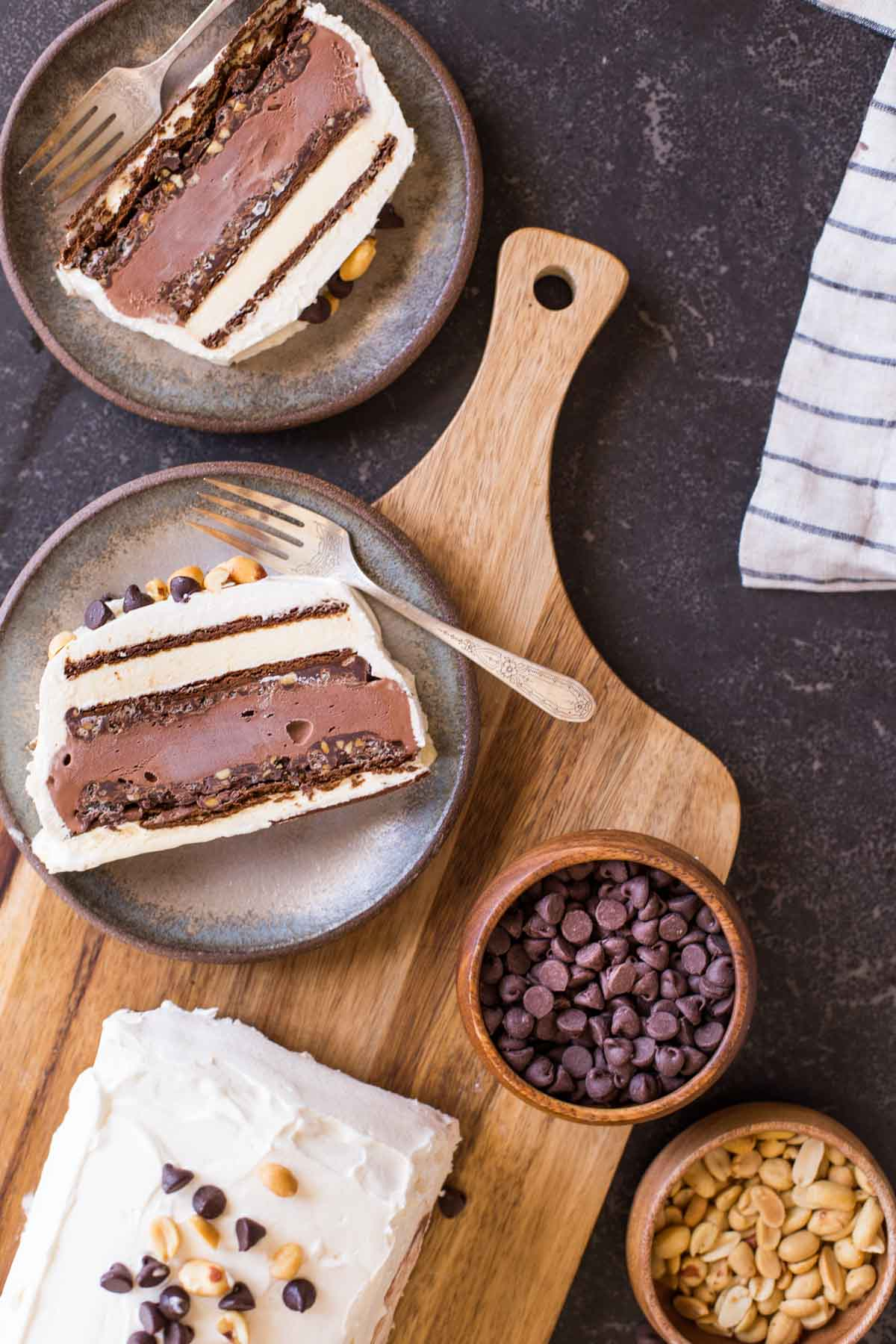 Two slices of Chocolate Peanut Butter Ice Cream Slice Cake on plates with forks, sitting next to the rest of the cake, along with a bowl of chocolate chips and a bowl of peanuts.