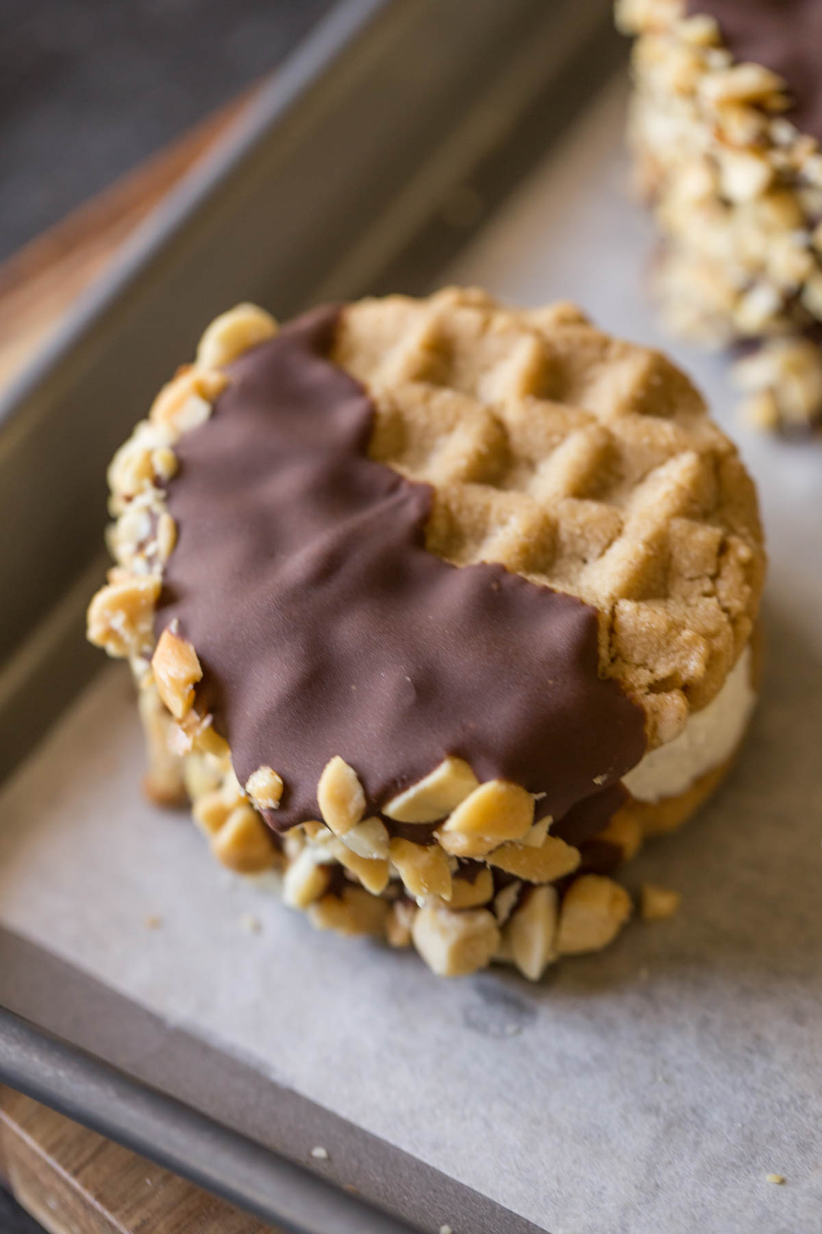 A Peanut Butter Cookie Ice Cream Sandwich on a parchment paper lined baking sheet.