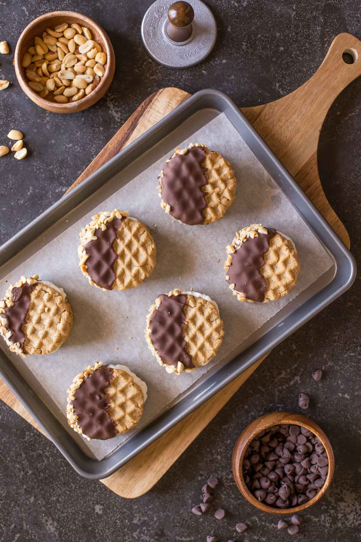 Peanut Butter Cookie Ice Cream Sandwiches on a parchment paper lined baking sheet, with a bowl of peanuts and a bowl of chocolate chips next to it.