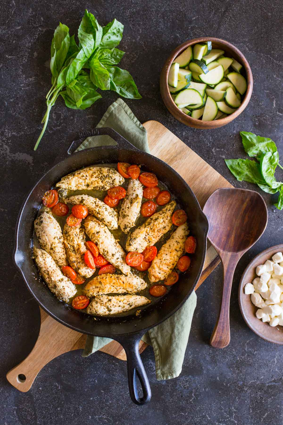 Cooked chicken and caramelized cherry tomatoes in a cast iron skillet, with some fresh basil, a bowl of sliced zucchini, a bowl of fresh mozzarella pearls and a wooden spoon next to the skillet, all to make the Pesto Chicken Skillet.