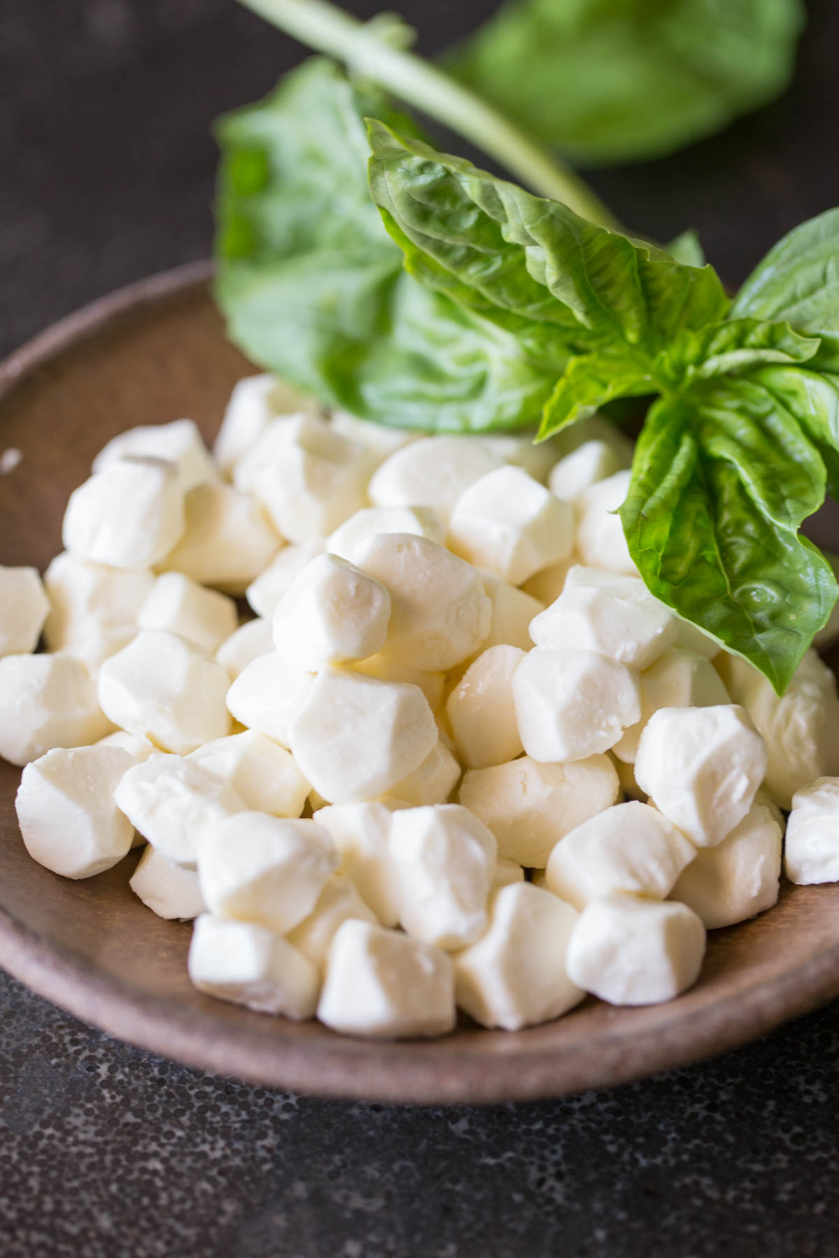 A bowl of fresh mozzarella pearls with some fresh basil for the Pesto Chicken Skillet.