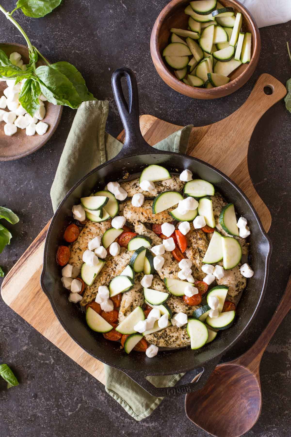 Cooked chicken and caramelized cherry tomatoes in a cast iron skillet, topped with zucchini slices and fresh mozzarella pearls, with some fresh basil, a bowl of sliced zucchini, a bowl of fresh mozzarella pearls and a wooden spoon next to the skillet.