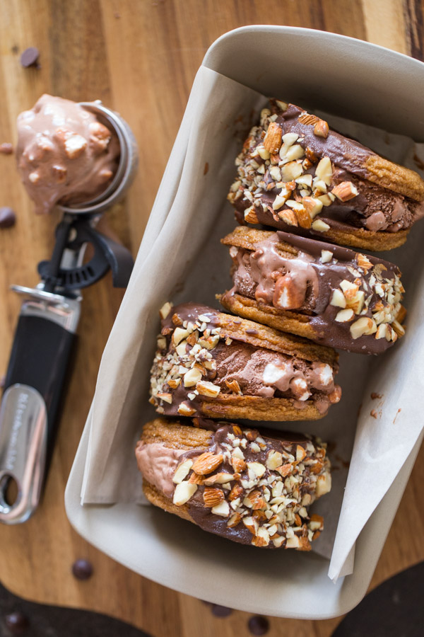 Four S'more Inspired Ice Cream Sandwiches in a loaf pan, with an ice cream scooper full of Rocky Road Ice Cream sitting next to the loaf pan.