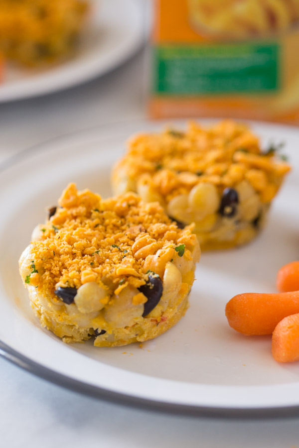 Two Southwestern Mac and Cheese cups on a plate with some carrot sticks.