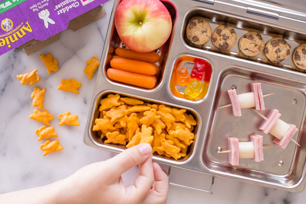 A lunch box with an apple, carrot sticks, Annie's Cheddar Bunnies, Annie's Cookie Bites, some gummy snacks, and ham and cheese on toothpicks.