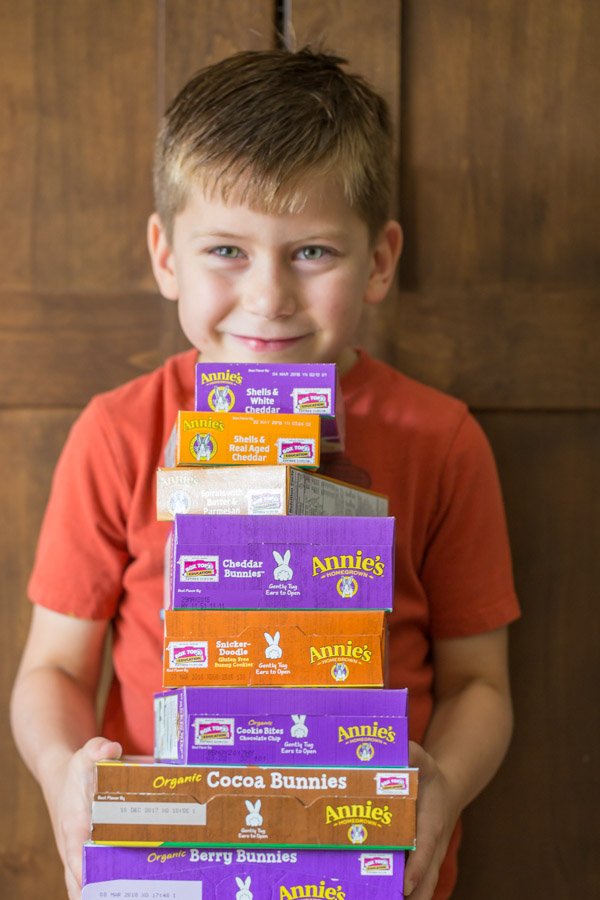 Little boy holding a stack of various Annie's products.