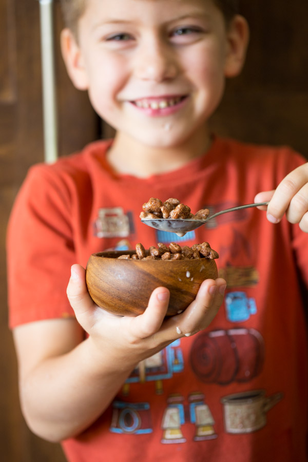 Little boy holding a small bowl of Annie's Cocoa Bunnies and milk.