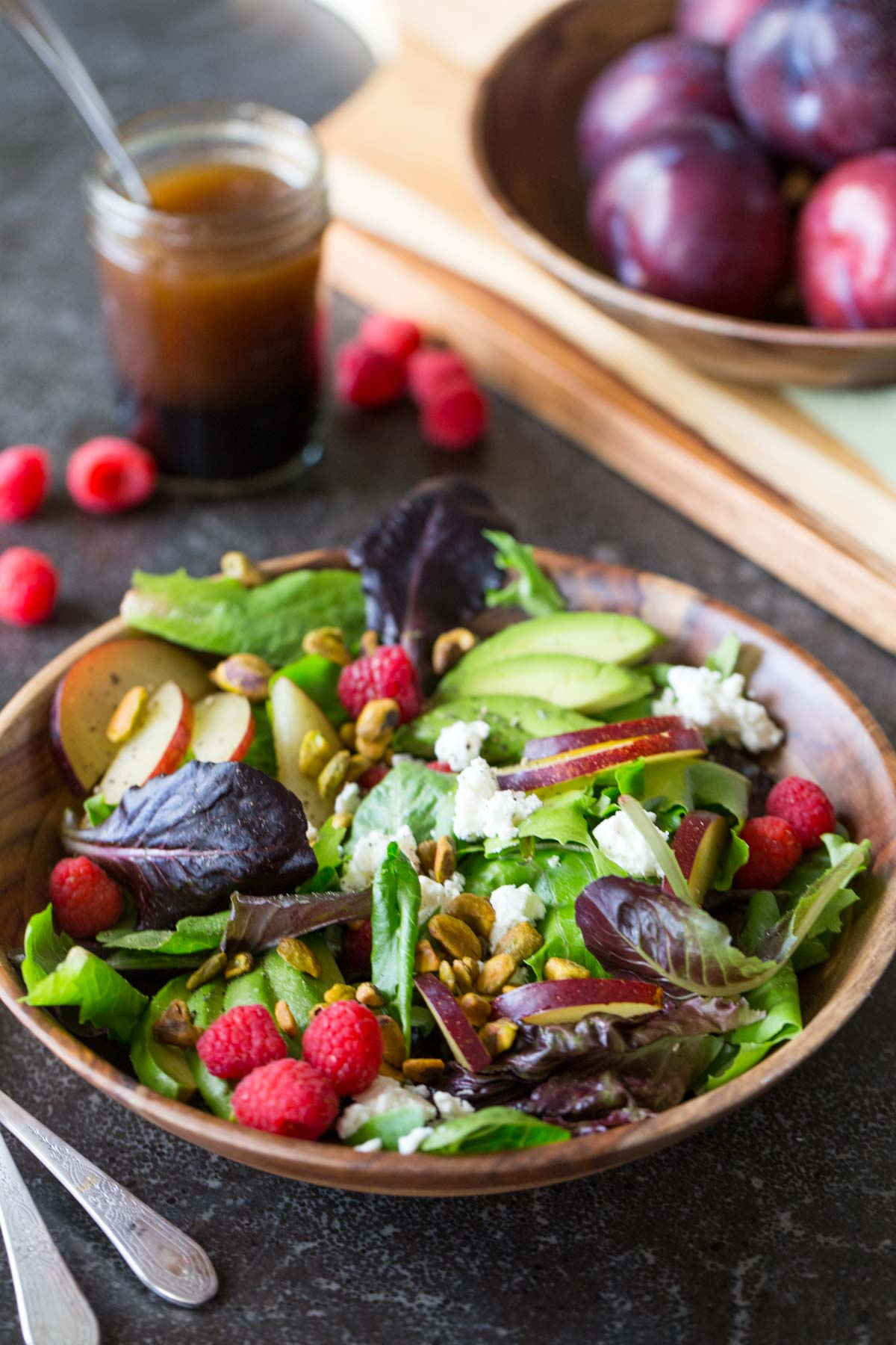 Summer Fruited Salad with Goat Cheese and Pistachios in a wood bowl, with a jar of homemade balsamic vinaigrette in the background along with a bowl of whole plums.